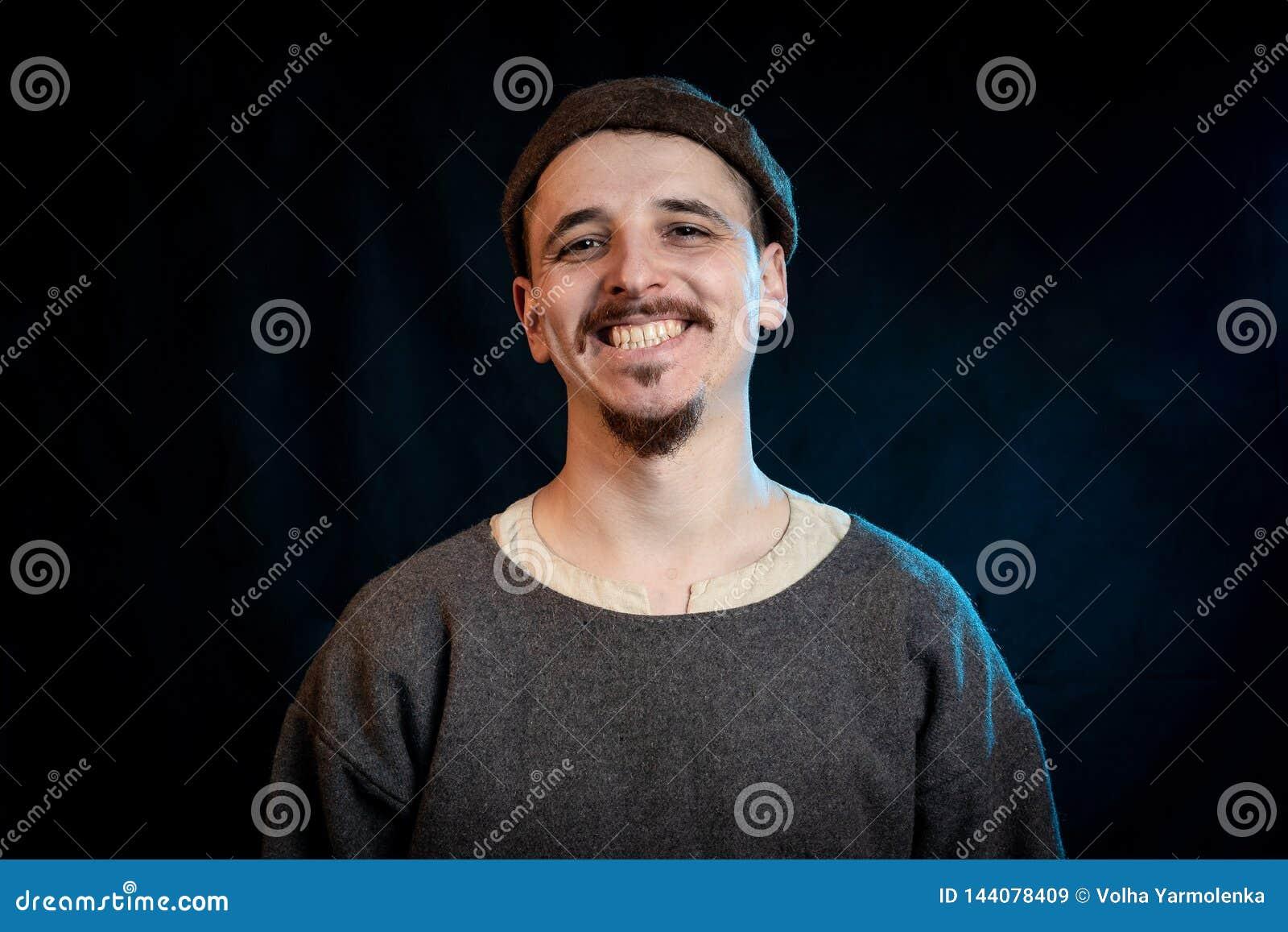 Ο νεαρός άνδρας στα περιστασιακά ενδύματα μαλλιού theearly των Μεσαιώνων που χαμογελά, κλείνει επάνω