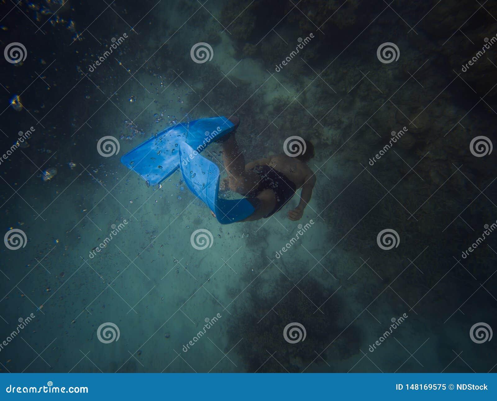 Ο νεαρός άνδρας Freediver κολυμπά υποβρύχιο με κολυμπά με αναπνευτήρα και βατραχοπέδιλα