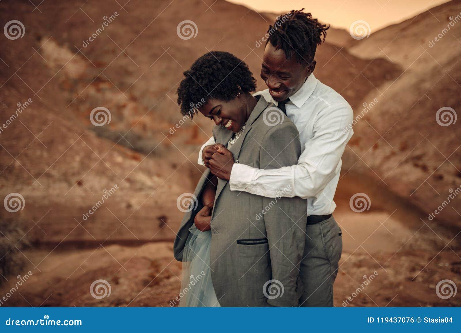 Ο νεόνυμφος αγκαλιάζει τη νύφη του που ντύνεται στο σακάκι του στο φαράγγι στο ηλιοβασίλεμα α
