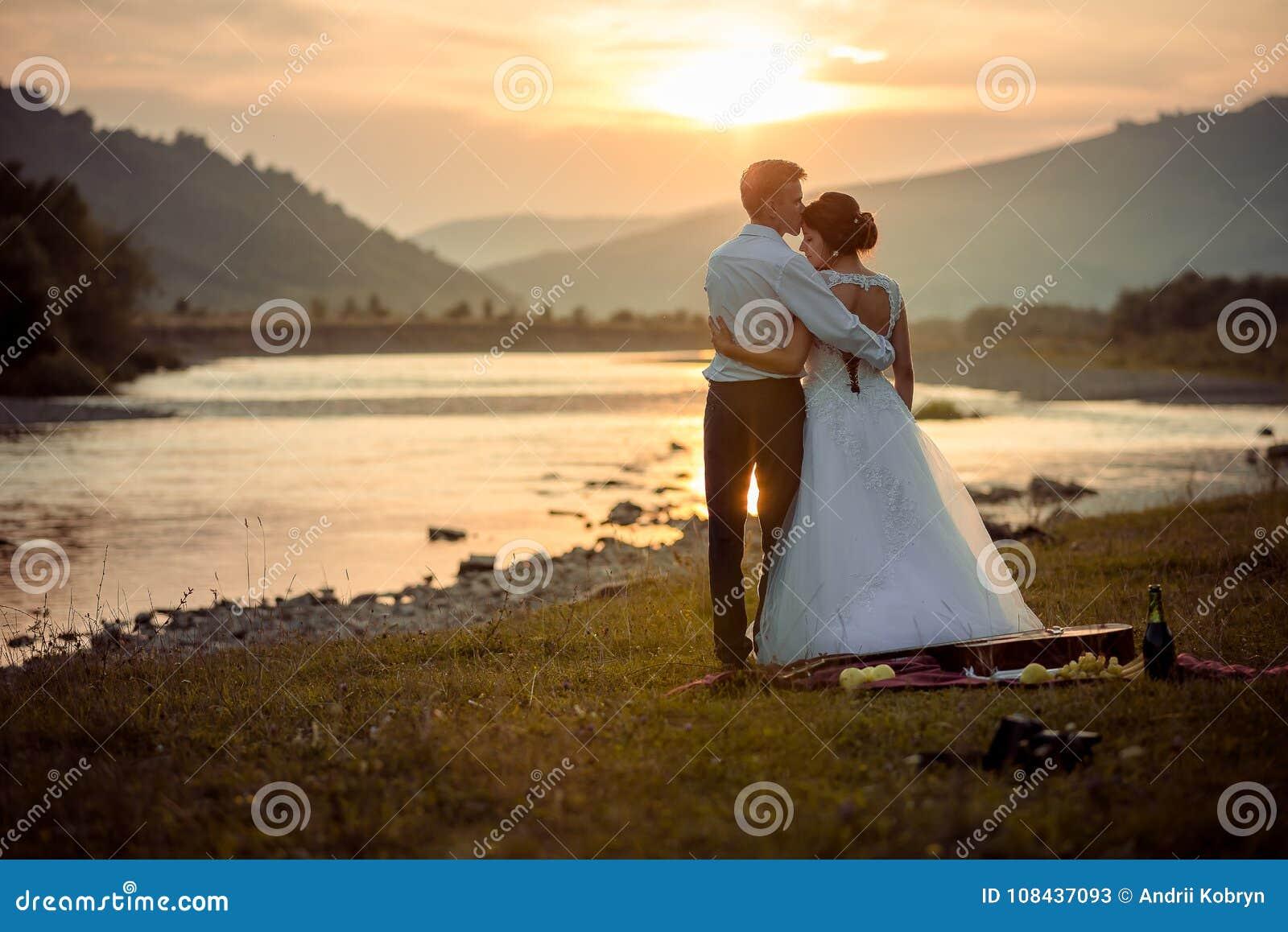 Ο νεόνυμφος φιλά μαλακά την πανέμορφη νύφη του στο μέτωπο κατά τη διάρκεια του ηλιοβασιλέματος Γαμήλιο πικ-νίκ στην όχθη ποταμού