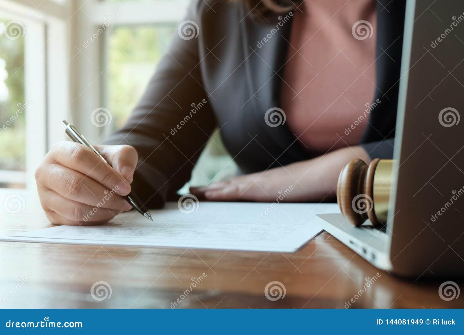 Ο νομικός σύμβουλος παρουσιάζει στον πελάτη μια υπογεγραμμένη σύμβαση με gavel και το νομικό νόμο δικαιοσύνη και νόμος δικηγόρων