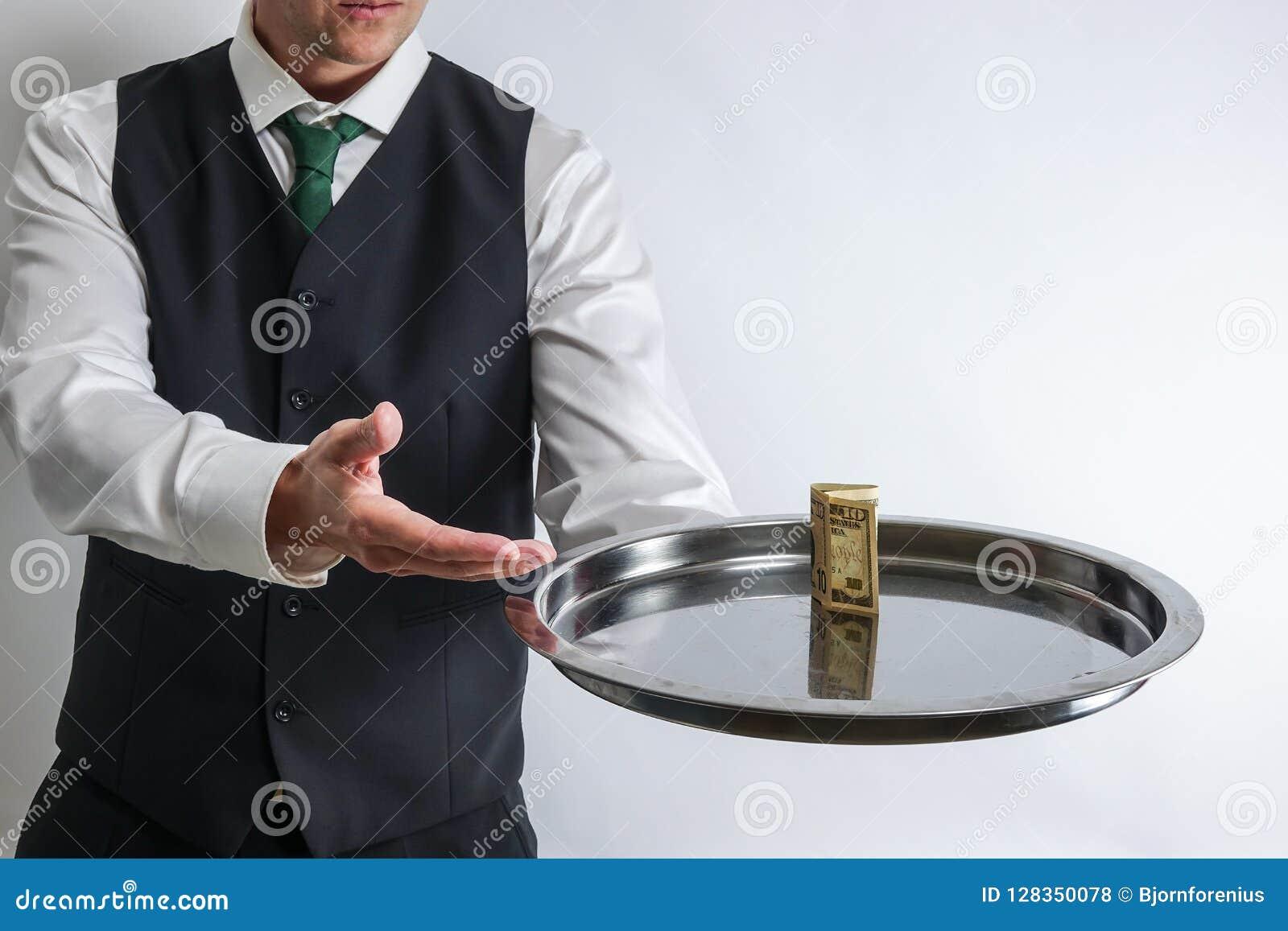 Ο οικονόμος/ο σερβιτόρος κρατά έναν ασημένιο δίσκο με έναν λογαριασμό δέκα δολαρίων