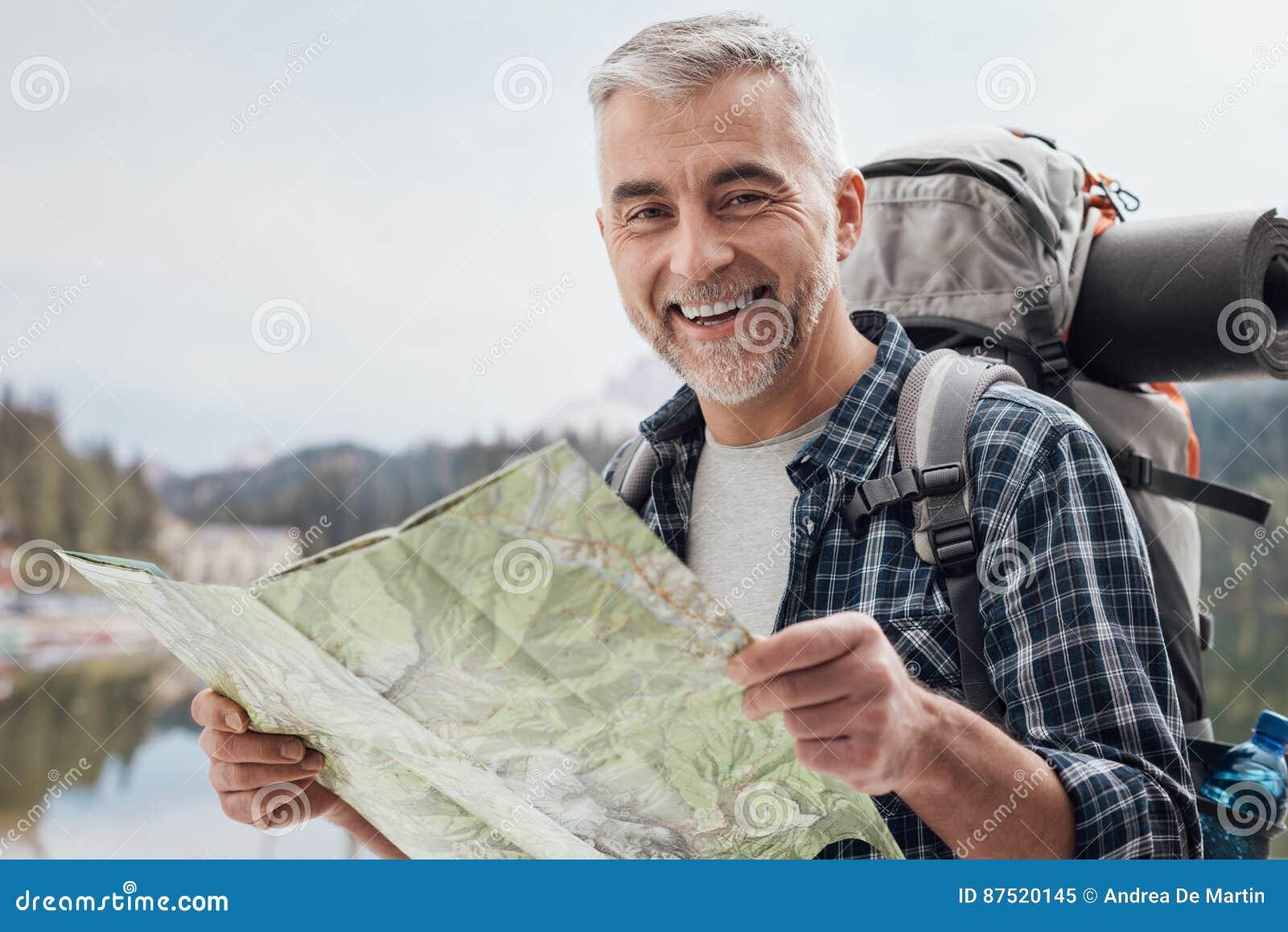 Οδοιπόρος που ψάχνει τις κατευθύνσεις σε έναν χάρτη
