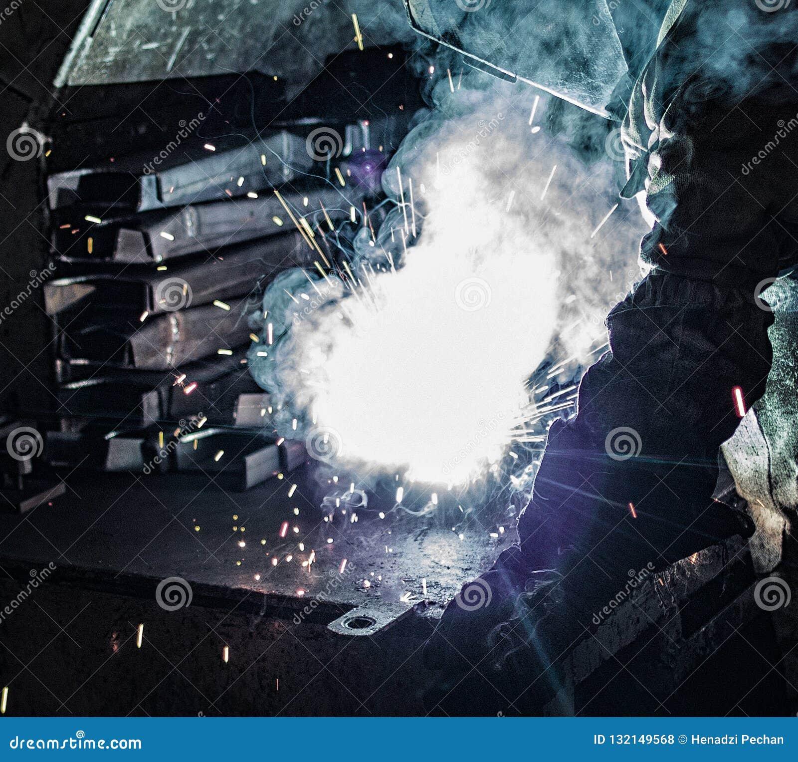 Ο οξυγονοκολλητής ενώνει στενά τα μέρη μετάλλων, πολλούς σπινθήρες και καπνούς, συγκόλληση, τόξο συγκόλλησης, φωτεινή λάμψη, κινη