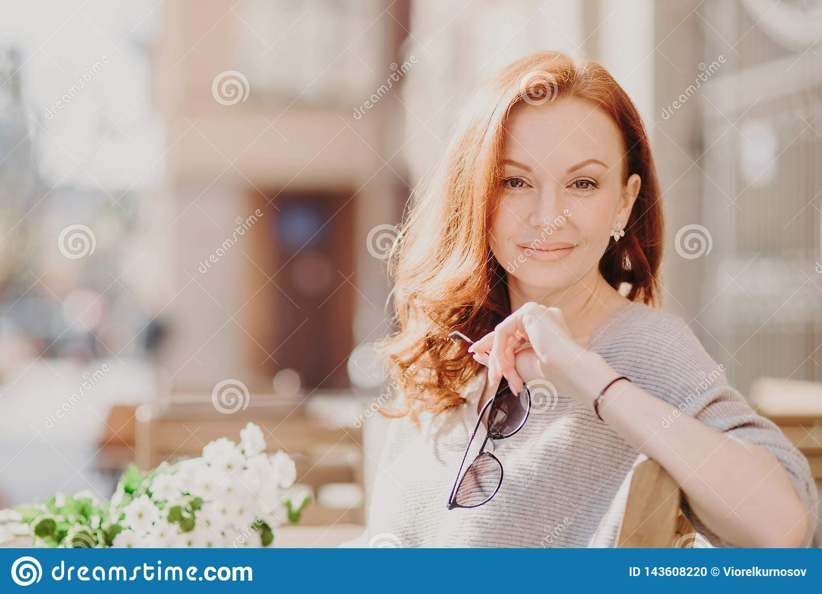 Ο οριζόντιος πυροβολισμός της ελκυστικής ευτυχούς κοκκινομάλλους γυναίκας κάθεται στον πάγκο, απολαμβάνει την ηλιόλουστη ημέρα, κ