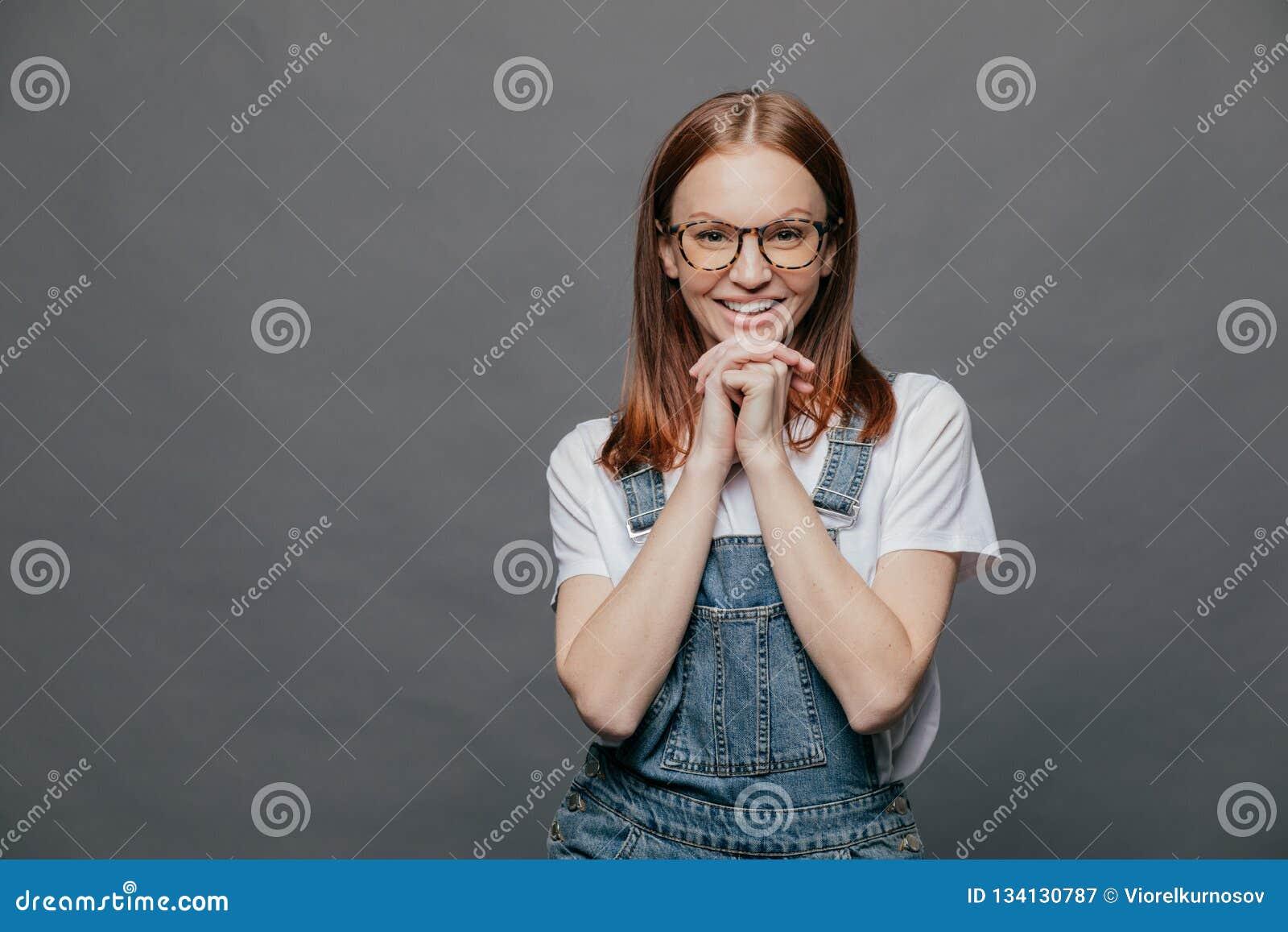 Ο οριζόντιος πυροβολισμός της ευτυχούς ευτυχούς γυναίκας κρατά και τα δύο χέρια κάτω από το πηγούνι, έχει το χαμόγελο στο πρόσωπο