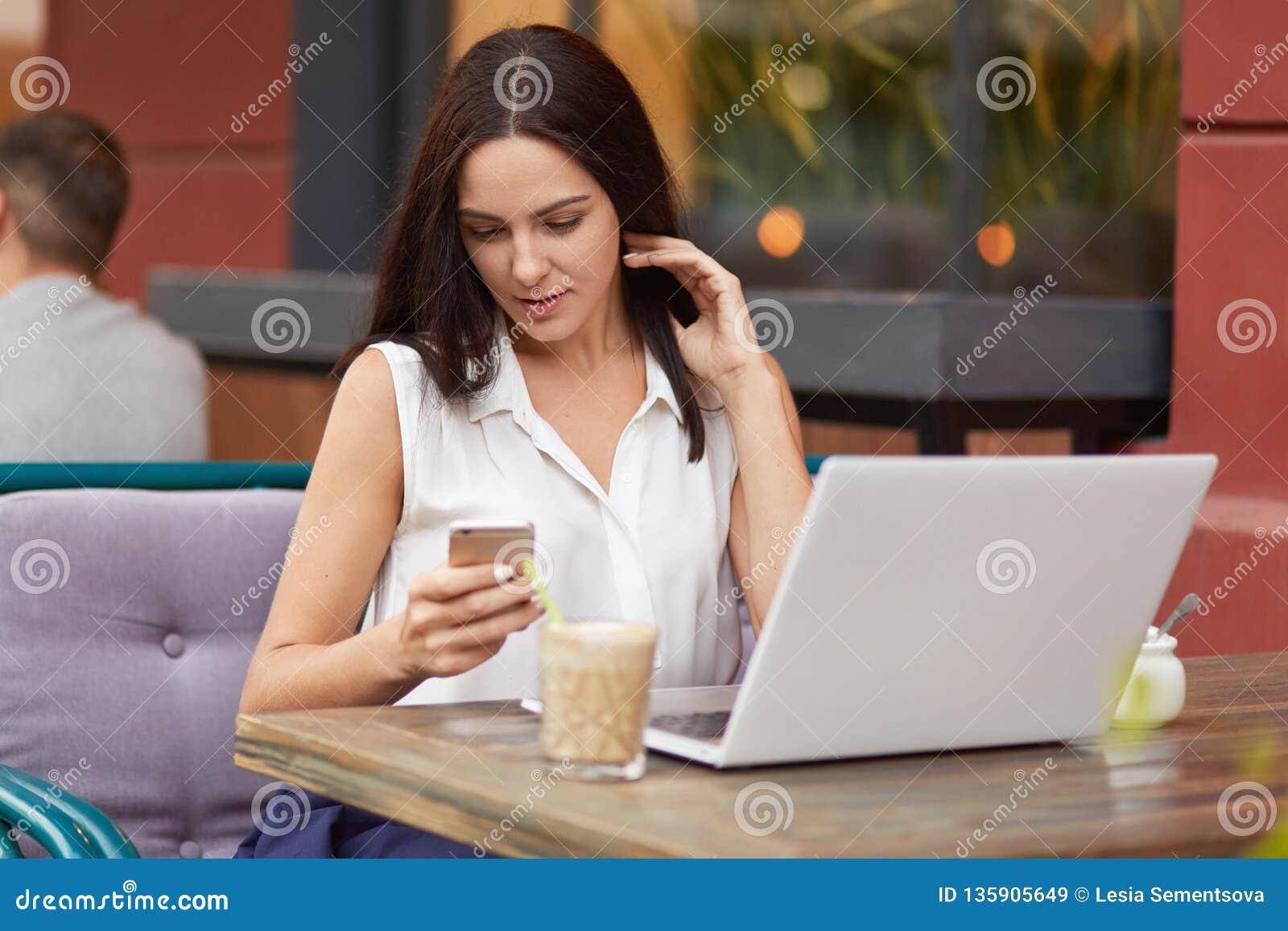 Ο οριζόντιος πυροβολισμός του πολυάσχολου θηλυκού freelancer κρατά το κινητό τηλέφωνο, μηνύματα κειμένου σε απευθείας σύνδεση, φο