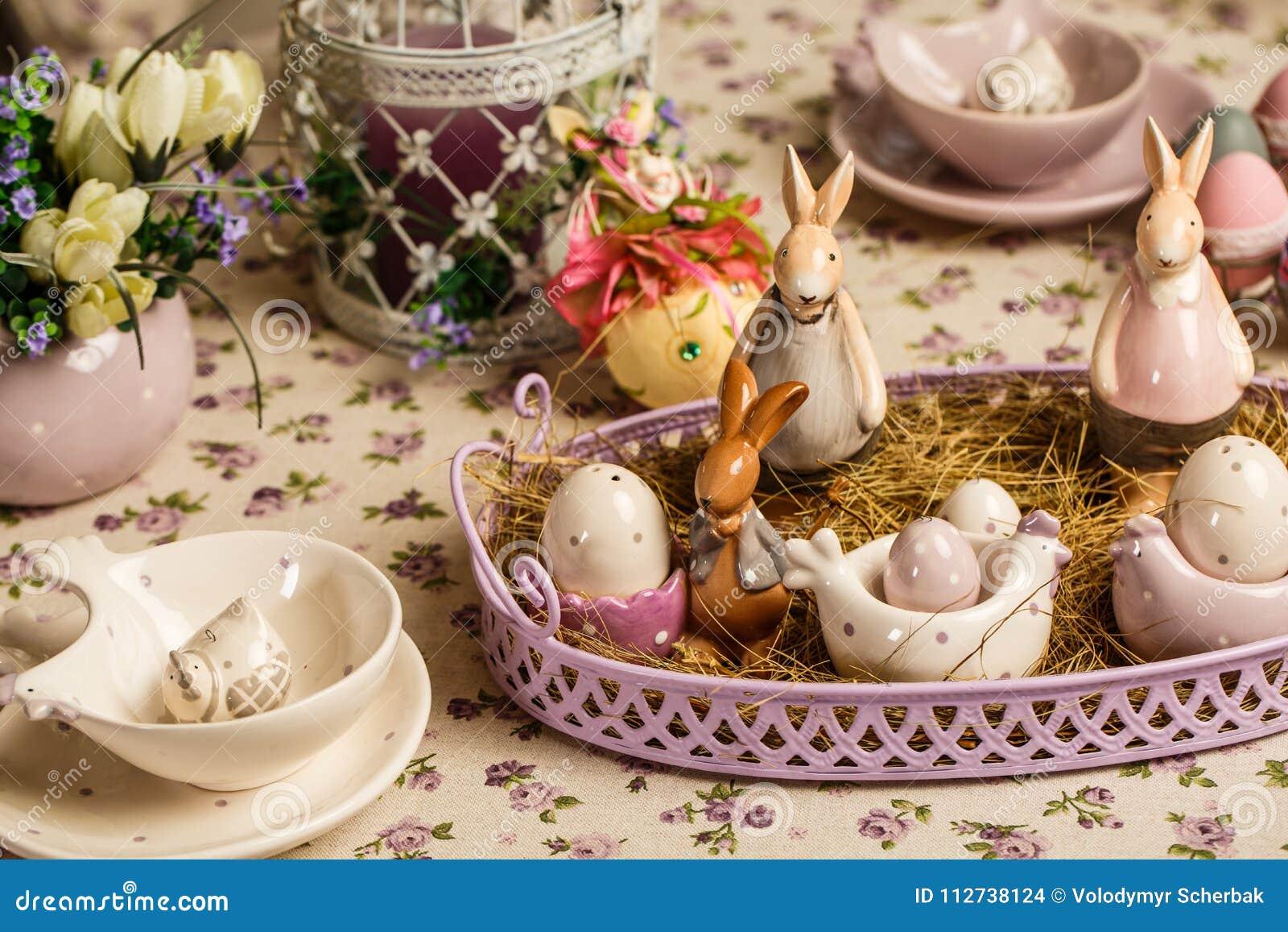 Ο πίνακας προγευμάτων Πάσχας με το τσάι, αυγά στα φλυτζάνια αυγών, άνοιξη ανθίζει στο βάζο και το ντεκόρ Πάσχας