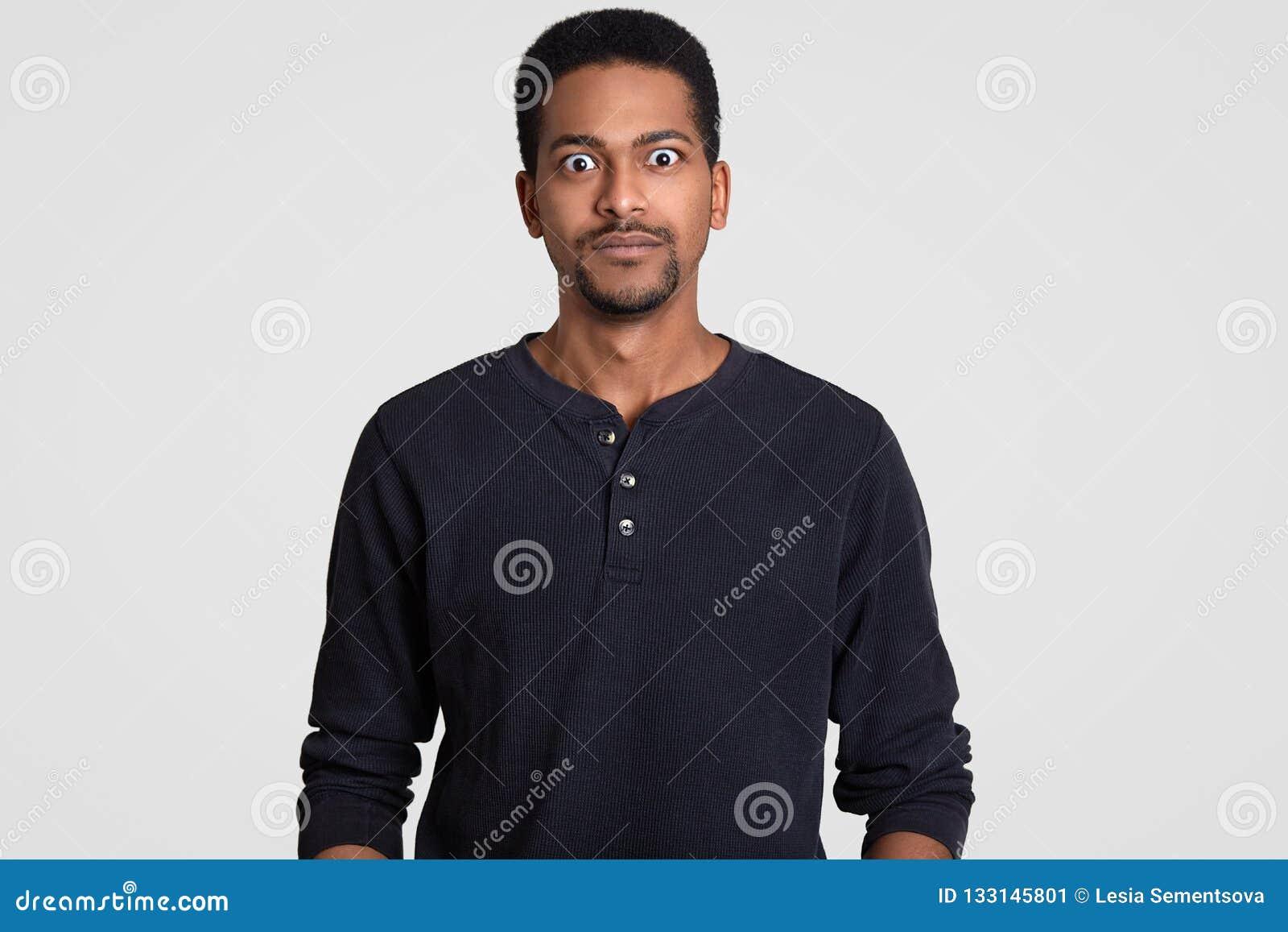 Ο παρακολουθημένος eyed όμορφος νεαρός άνδρας εξετάζει στην κατάπληξη τη κάμερα, ντύνει λίγη γενειάδα, άνετα, που μένει έκπληκτη