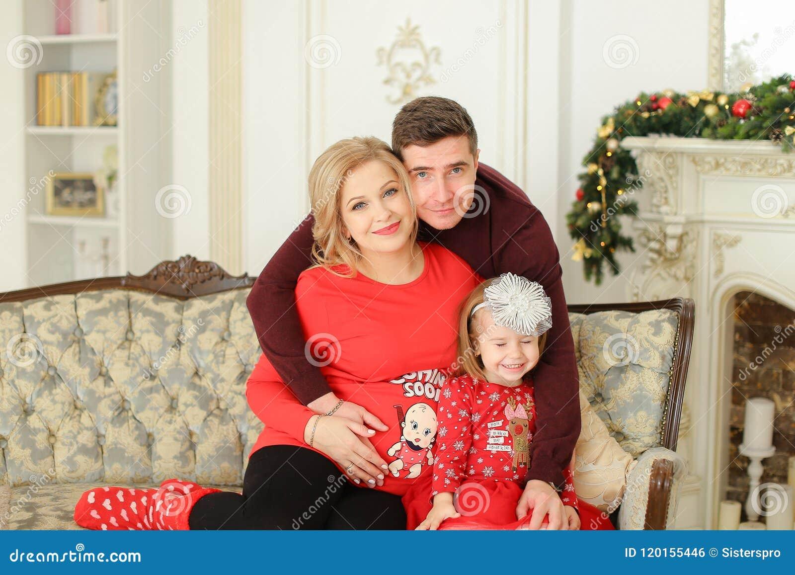Ο πατέρας και η έγκυος συνεδρίαση μητέρων με λίγη κόρη στον καναπέ διακόσμησαν πλησίον την εστία