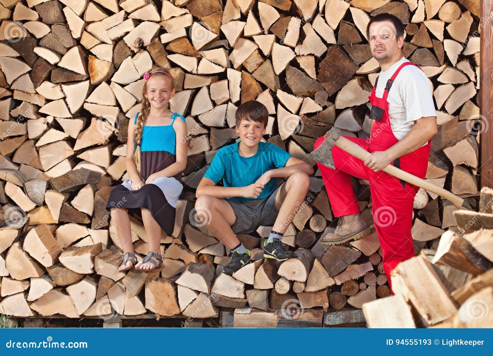 Ο πατέρας και τα παιδιά προετοιμάστηκαν να τεμαχίσουν το καυσόξυλο και να το συσσωρεύσουν σε ένα wo