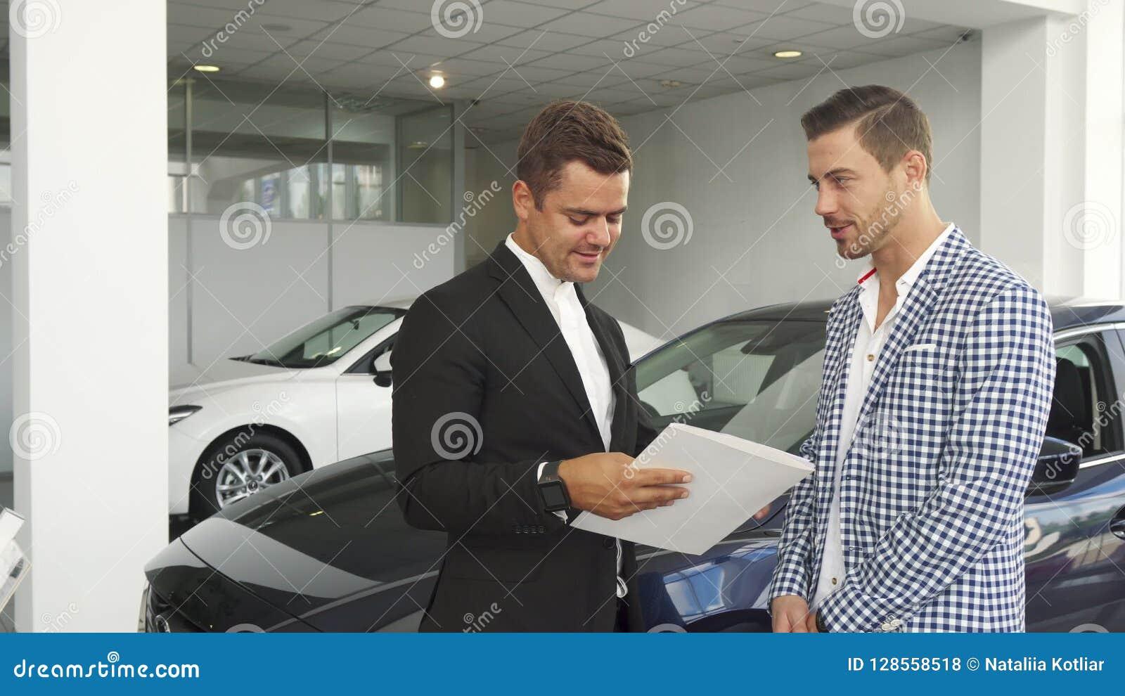 Ο πιθανοί αγοραστής και ο πωλητής διαβάζουν τα χαρακτηριστικά του αυτοκινήτου