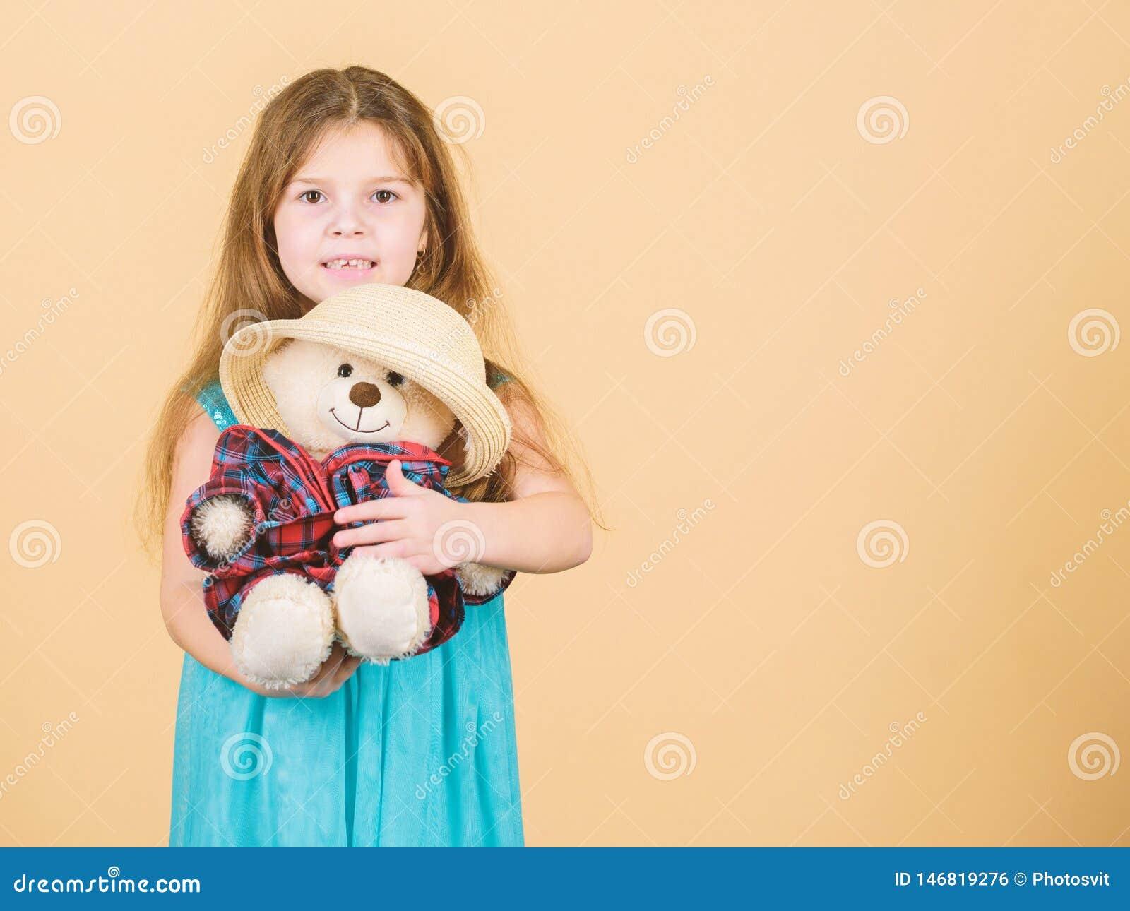 Ο πιό χαριτωμένος πάντα Το μικρό κορίτσι παιδιών αγκαλιάζει προσεκτικά το μαλακό παιχνίδι teddy αντέχει το μπεζ υπόβαθρο Τρυφερές