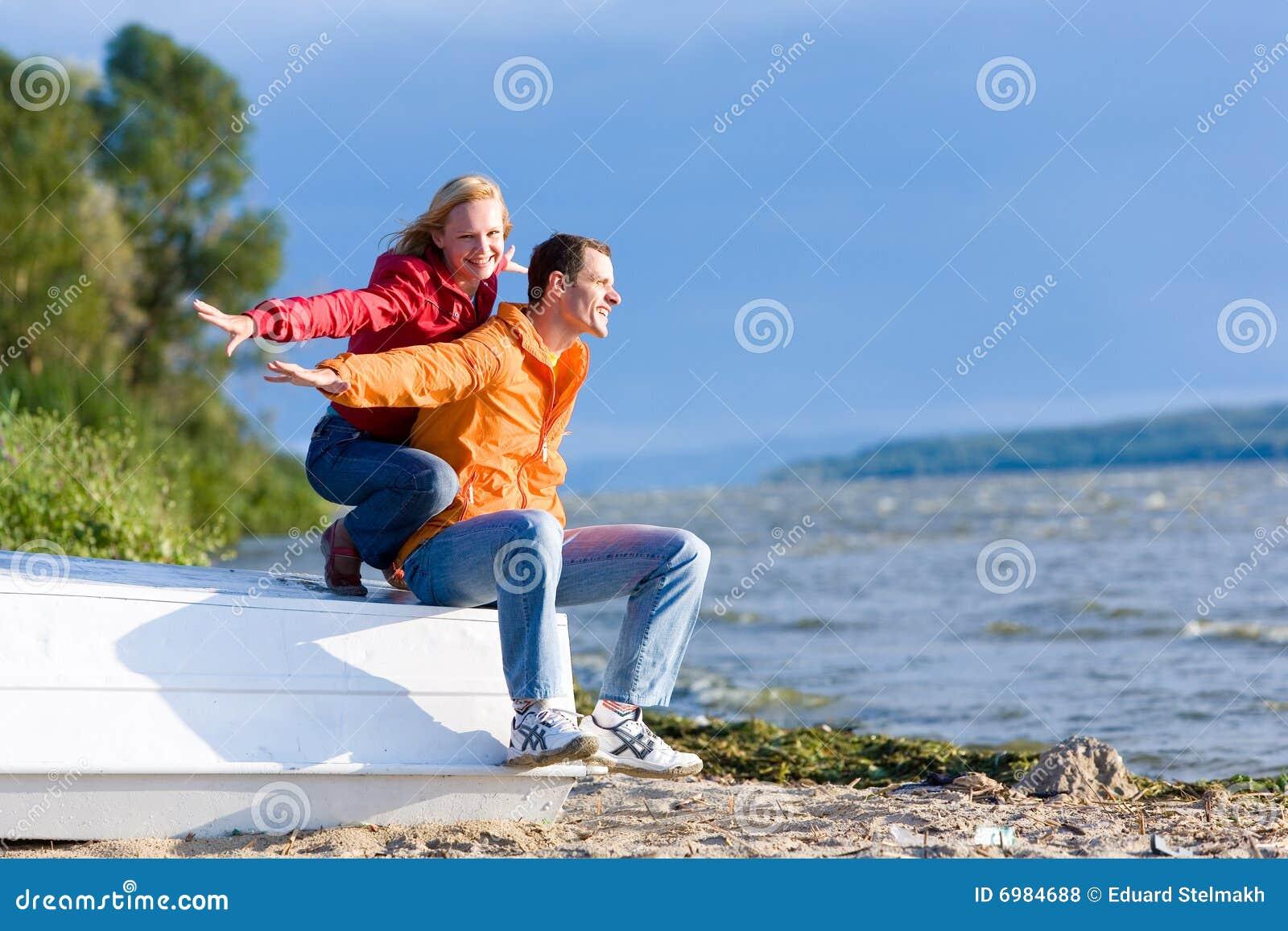 ο ποταμός αγάπης ζευγών ακτών βαρκών κάθεται τις νεολαίες