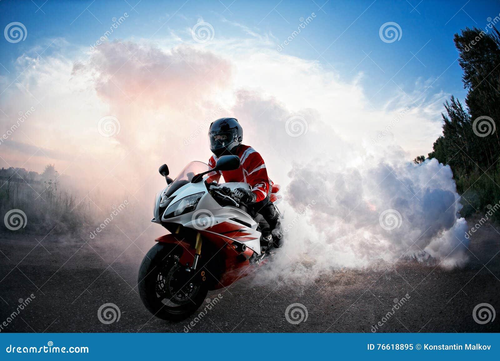 Ο ποδηλάτης που μένει στο δρόμο ποδηλάτων με τον καπνό της ρόδας, έγκαυμα έξω στο moto παρουσιάζει αέρας ηλιοβασιλέματος θύελλας