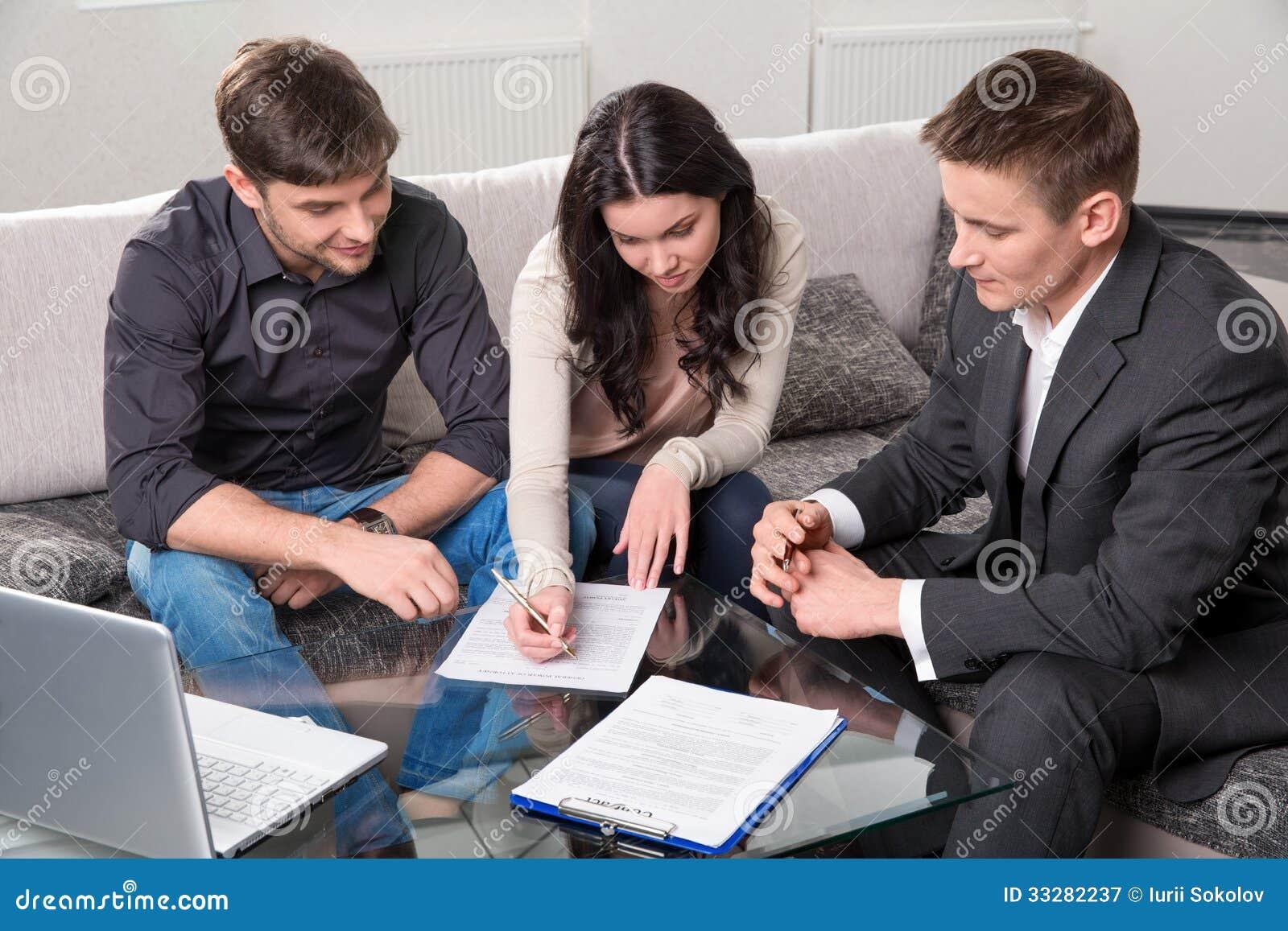 Ο πράκτορας συμβουλεύει το ζεύγος, που υπογράφει τα έγγραφα