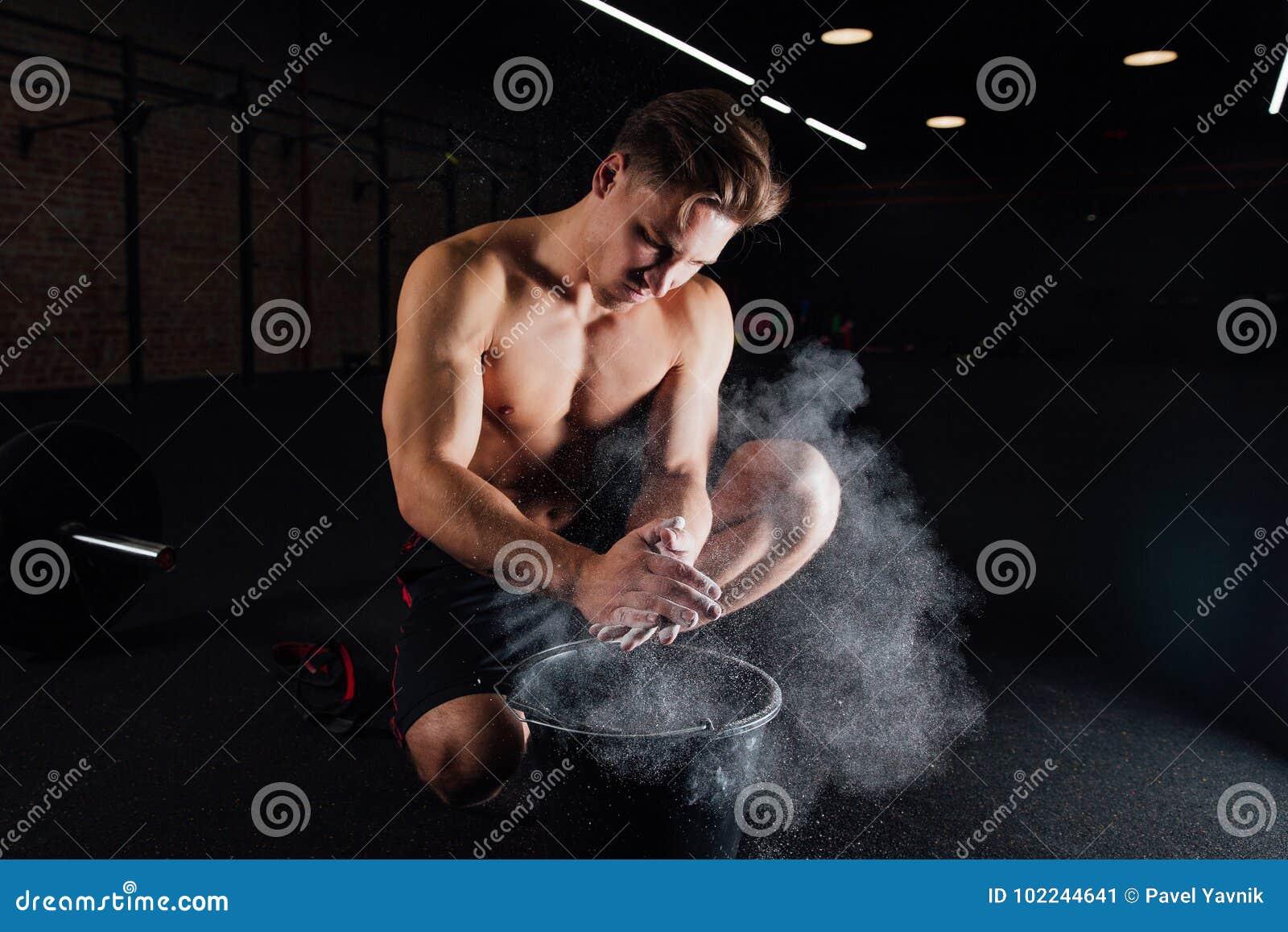 Ο πρότυπος εκπαιδευτής ικανότητας τρίβει τα χέρια του με την κιμωλία και talc έτσι ώστε τα δάχτυλα δεν γλιστρούν ή δεν γλιστρούν