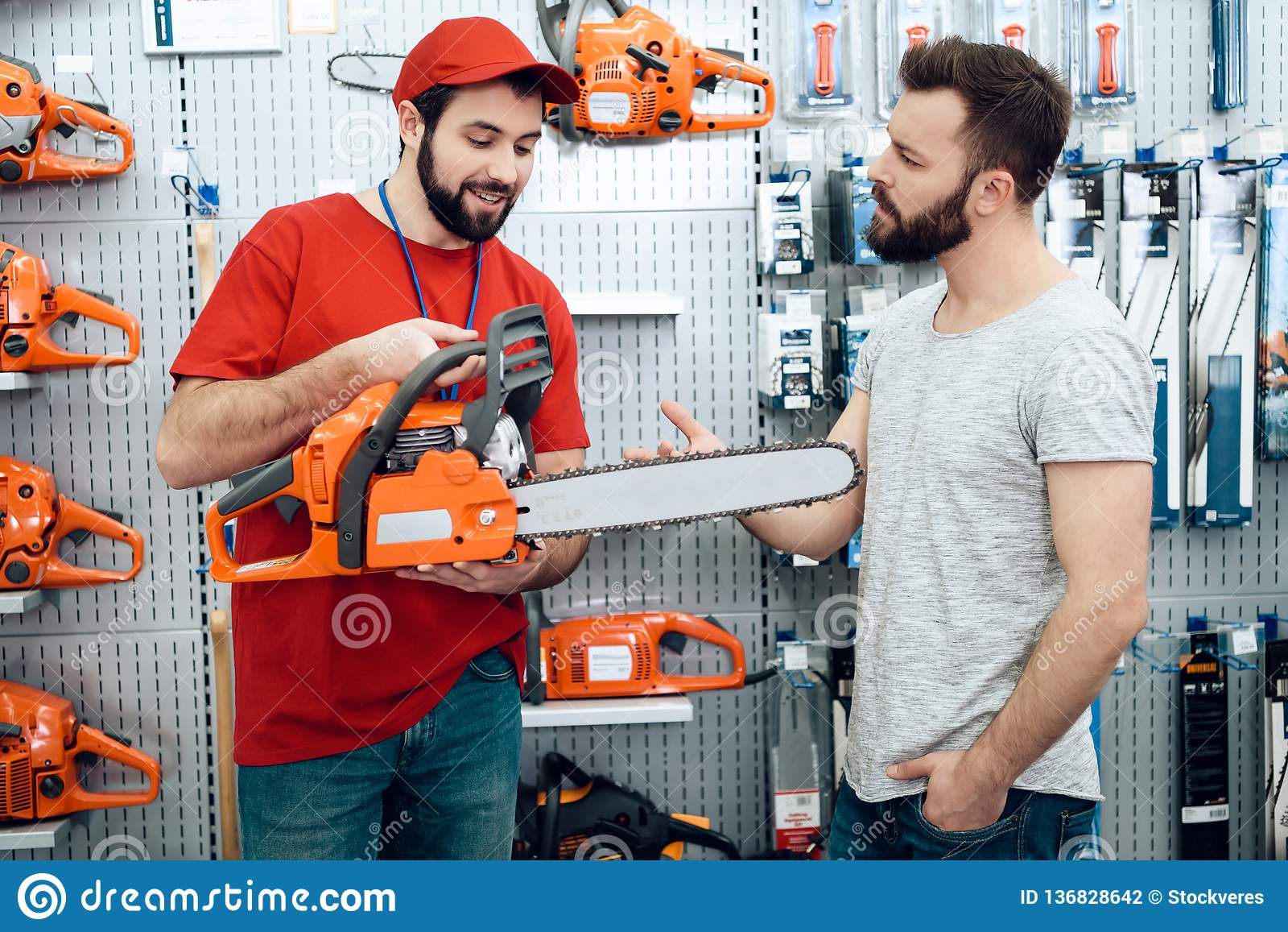 Ο πωλητής παρουσιάζει γενειοφόρο νέο αλυσιδοπρίονο πελατών στο κατάστημα εργαλείων δύναμης