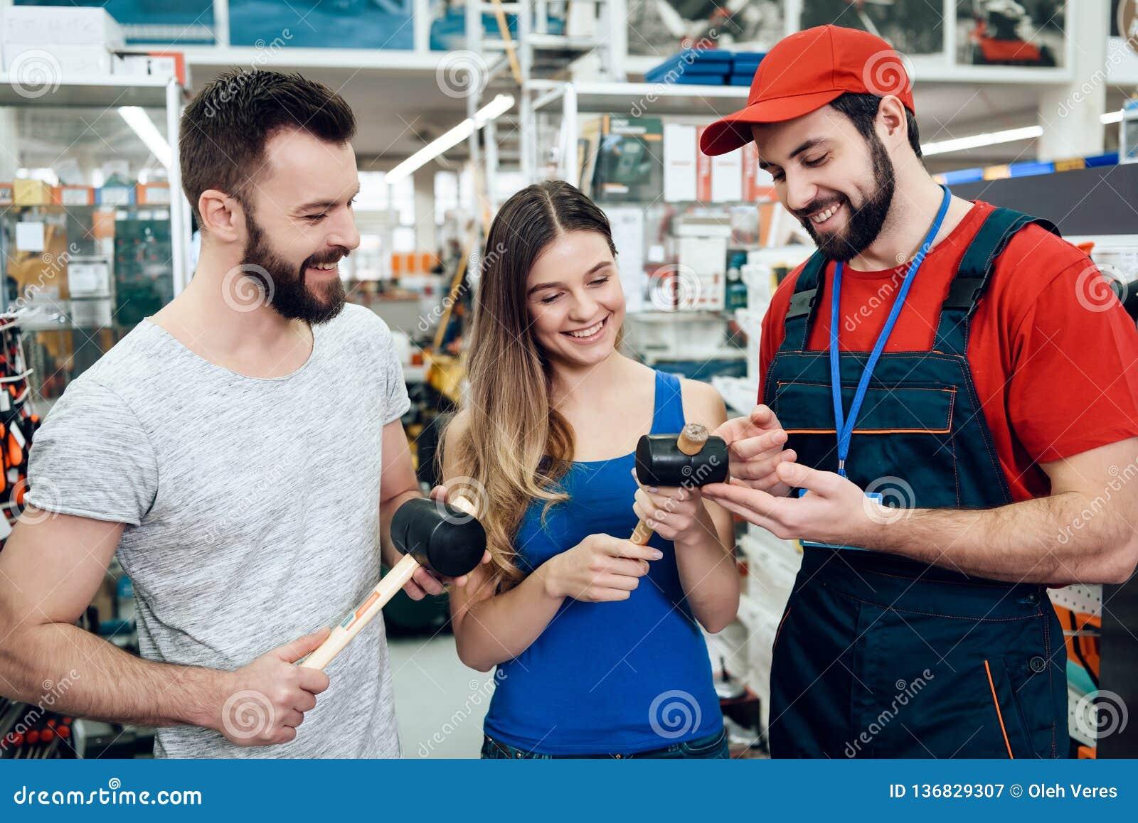 Ο πωλητής παρουσιάζει ζεύγος των νέων λαστιχένιων σφυριών πελατών στο κατάστημα εργαλείων δύναμης