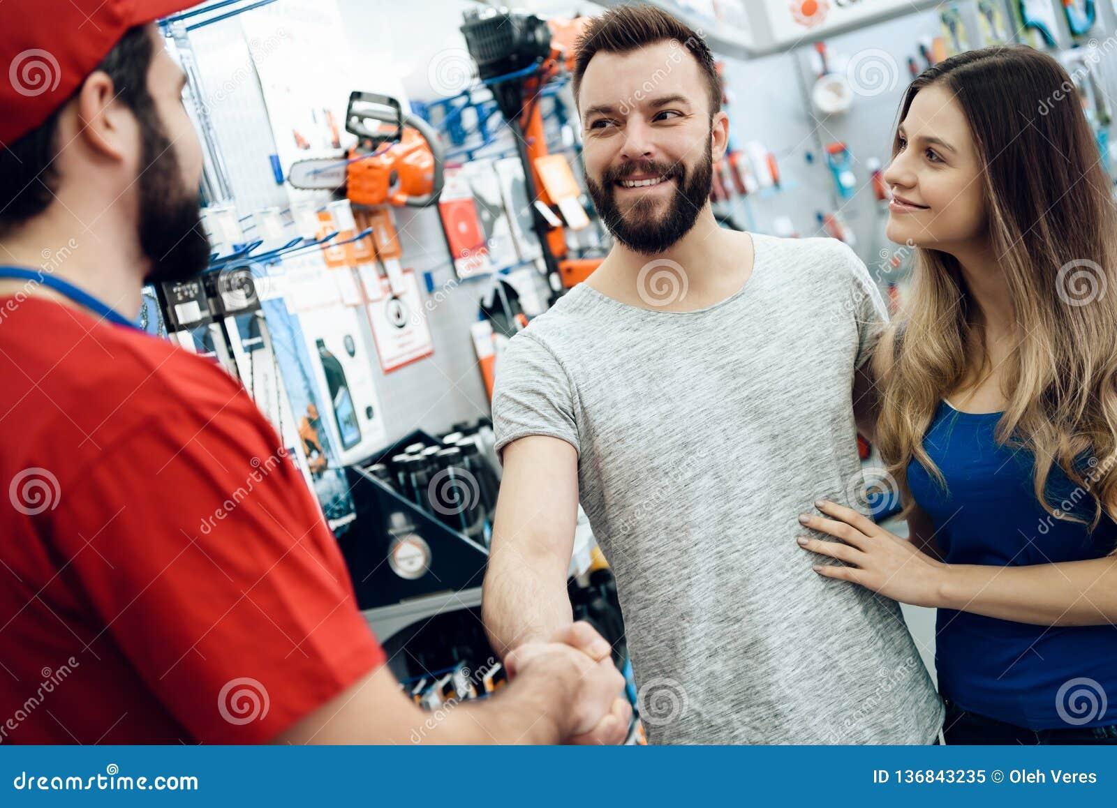 Ο πωλητής τινάζει τα χέρια με το γενειοφόρο πελάτη στο κατάστημα εργαλείων δύναμης