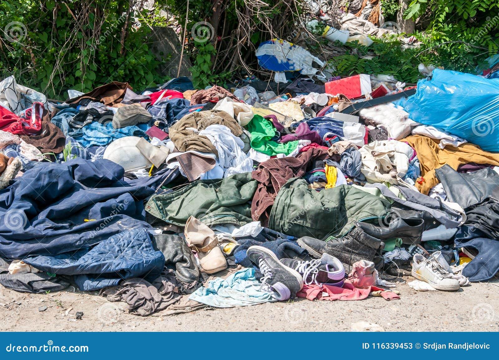 Ο σωρός των παλαιών ενδυμάτων και των παπουτσιών πέταξε στη χλόη ως παλιοπράγματα και απορρίματα, που ρυπαίνουν και που μολύνουν