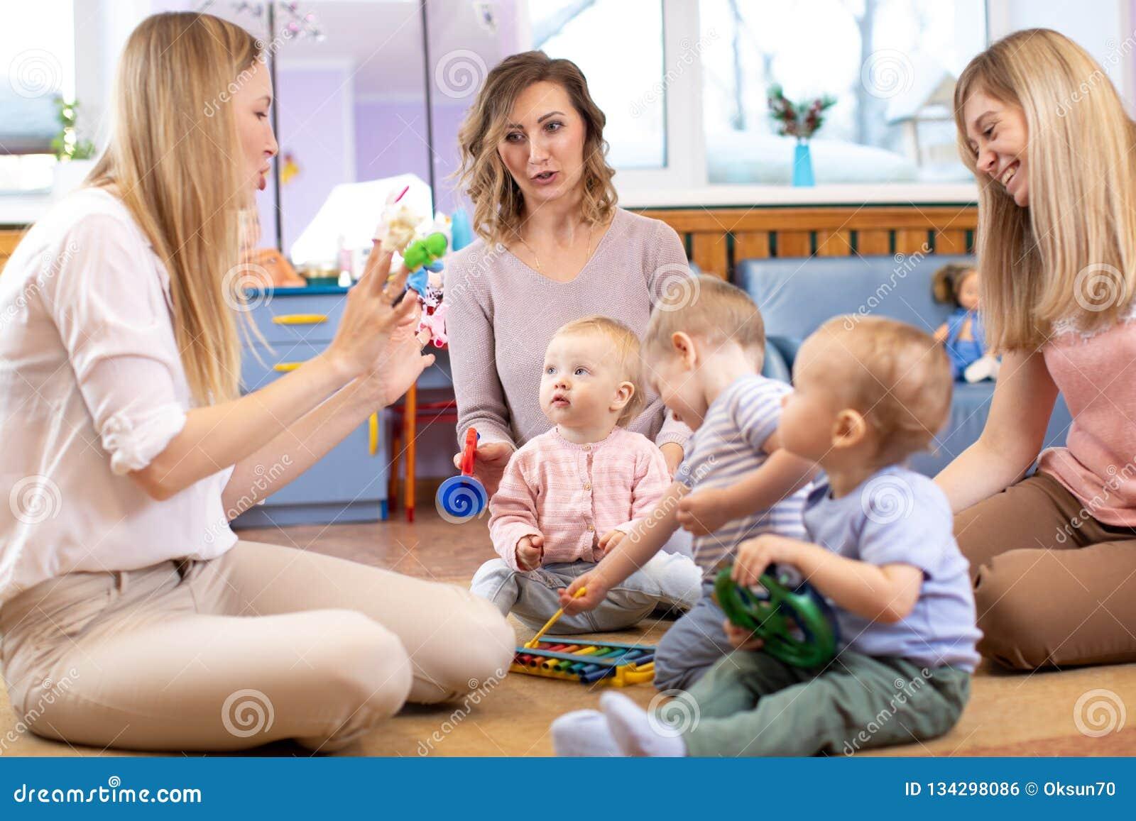 Ο σύμβουλος και χρονών τα μωρά 1 παίζουν με τα εκπαιδευτικά παιχνίδια στον παιδικό σταθμό ή το κέντρο φύλαξης