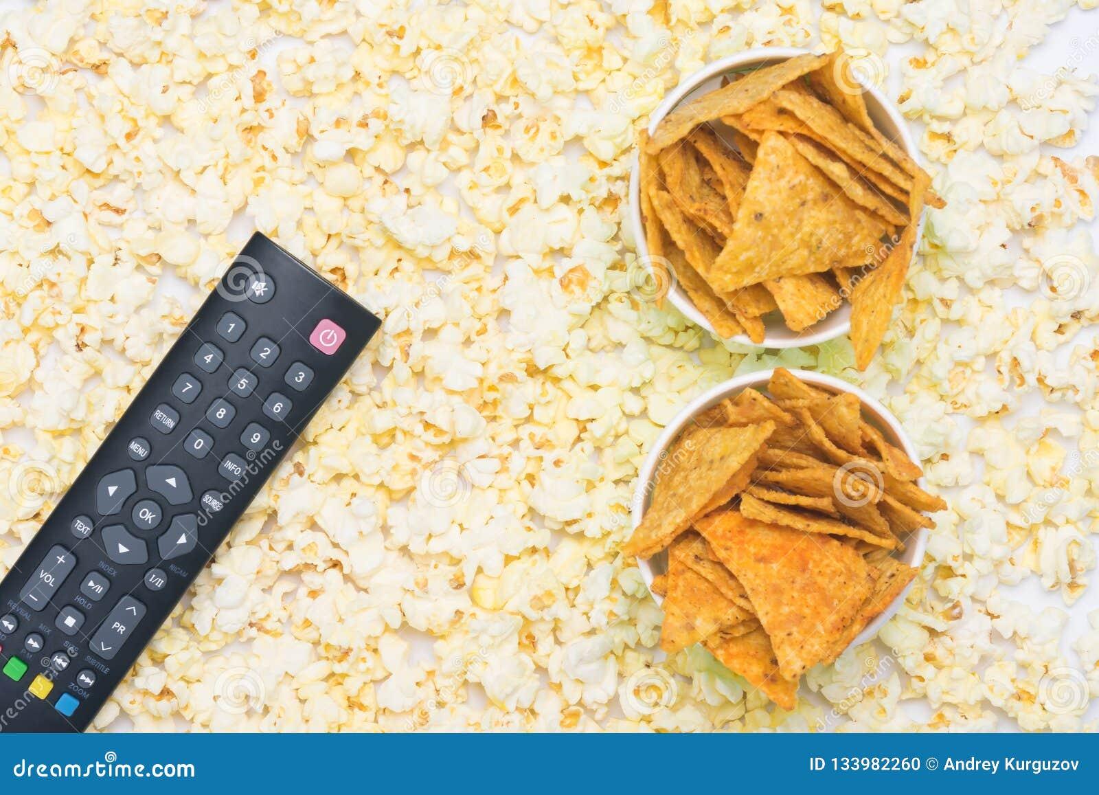Ο τηλεχειρισμός με τα κουμπιά βρίσκεται popcorn δύο φλυτζάνια εγγράφου που γεμίζουν με με τα nachos