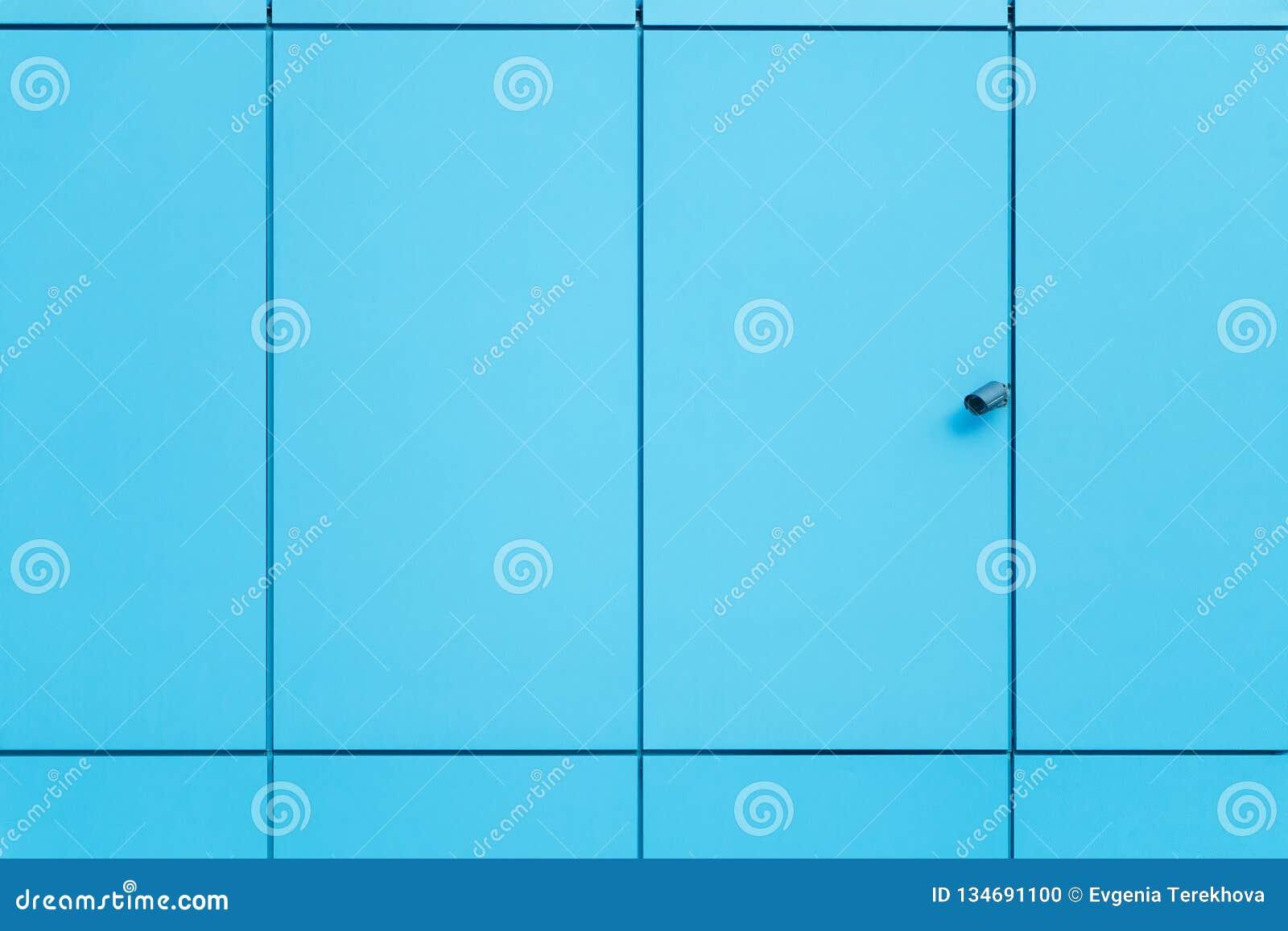 Ο τοίχος καλύπτεται με τις μπλε επιτροπές και τα κάμερα ασφαλείας περιποίησης αφηρημένος αρχιτεκτονικός ουρανός λεπτομέρειας οικο