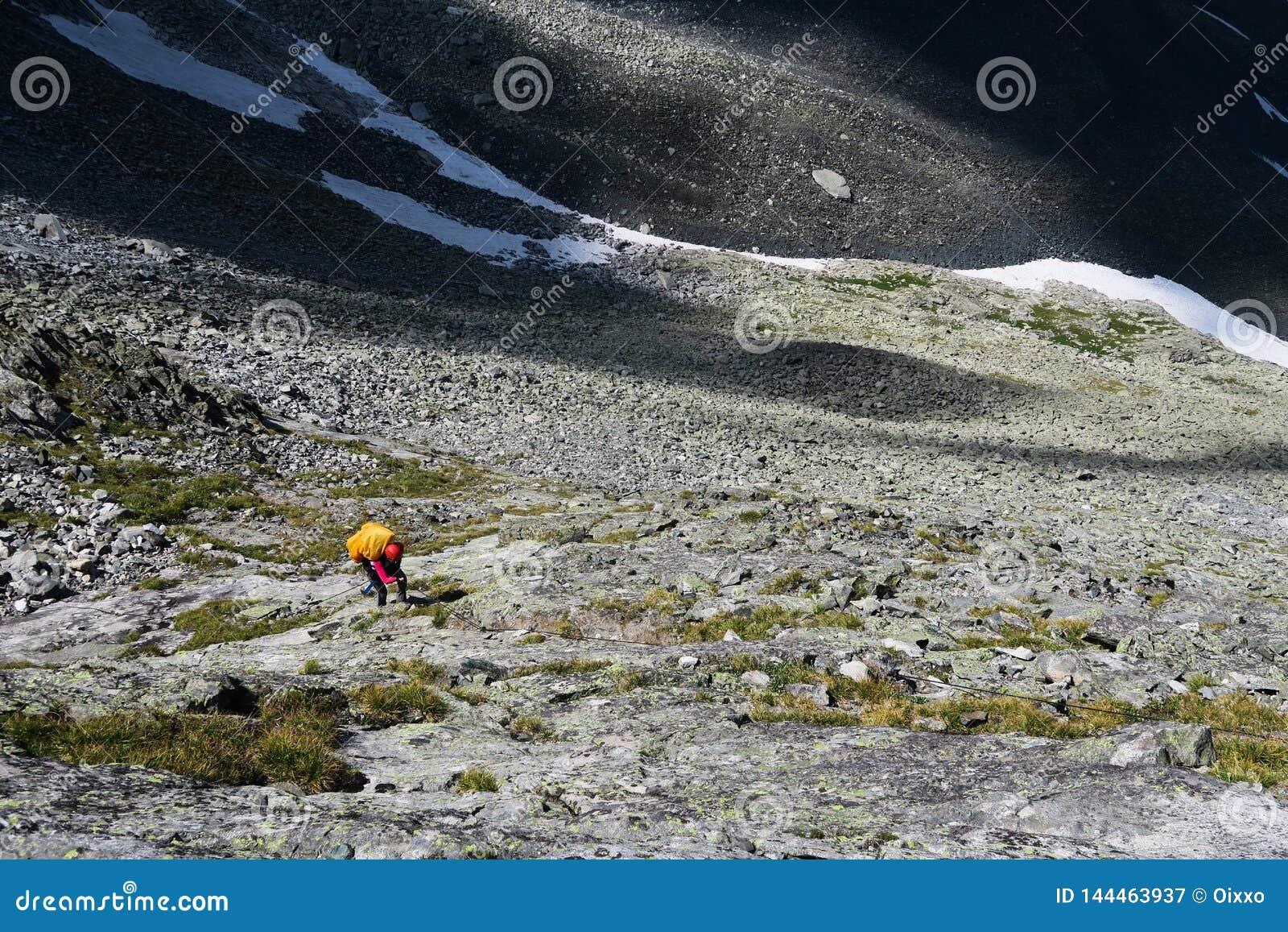 Ο τουρίστας αναρριχείται επάνω στις πέτρες στα βουνά Να ανεβεί το δύσκολο moraine