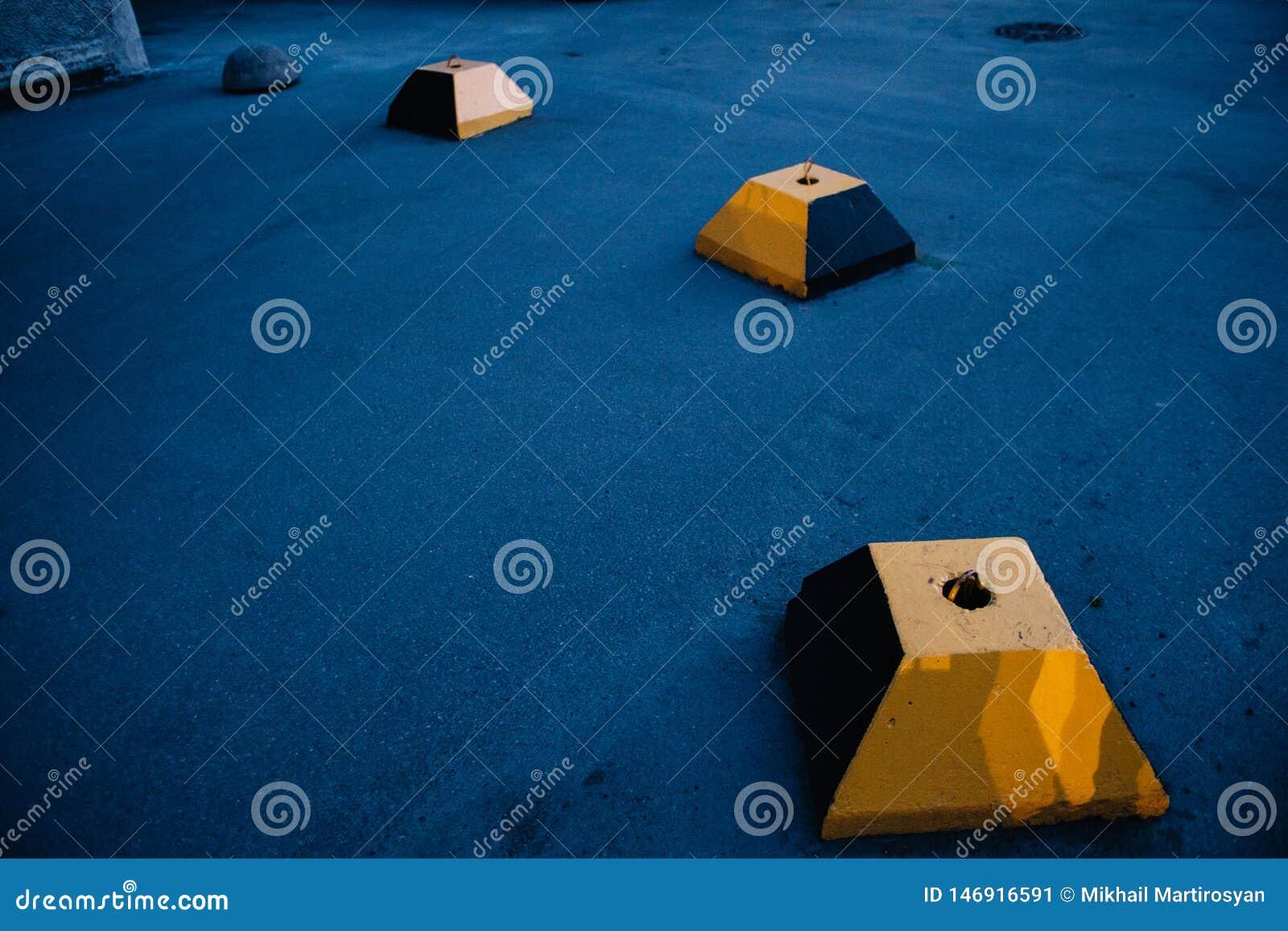 Ο τσιμεντένιος ογκόλιθος της περικομμένης κίτρινης πυραμίδας στα πλαίσια της μπλε ασφάλτου
