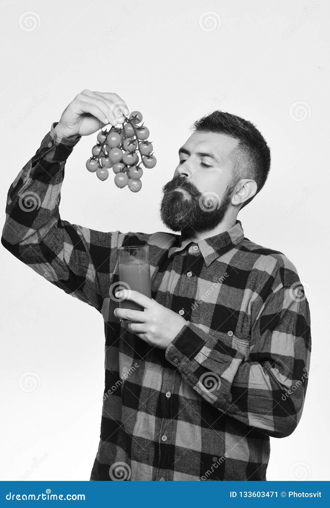 Ο τύπος με το homegrown άτομο συγκομιδών με τη γενειάδα κρατά το χυμό