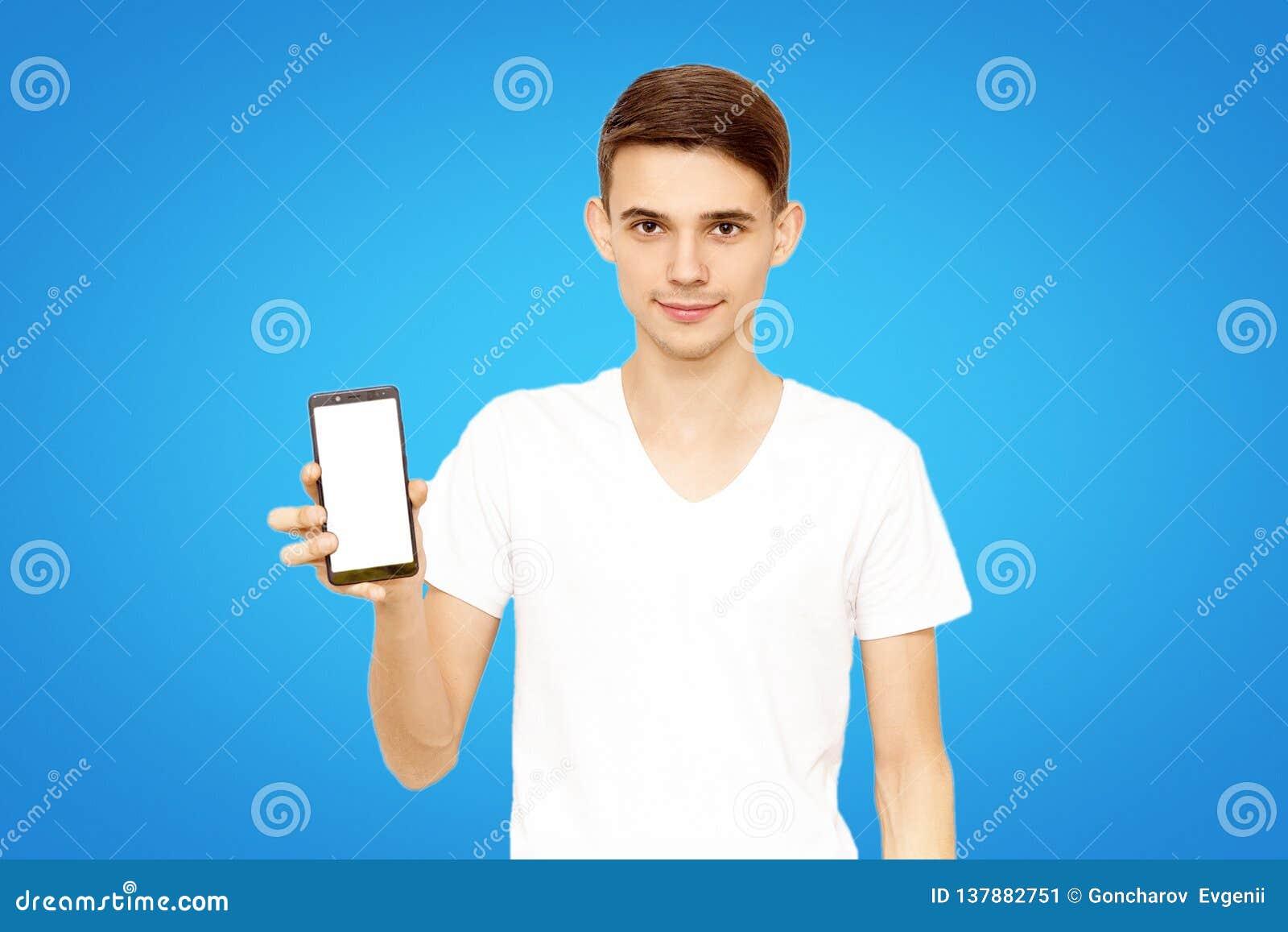 Ο τύπος στην άσπρη μπλούζα διαφημίζει το τηλέφωνο, σε ένα μπλε υπόβαθρο στο στούντιο