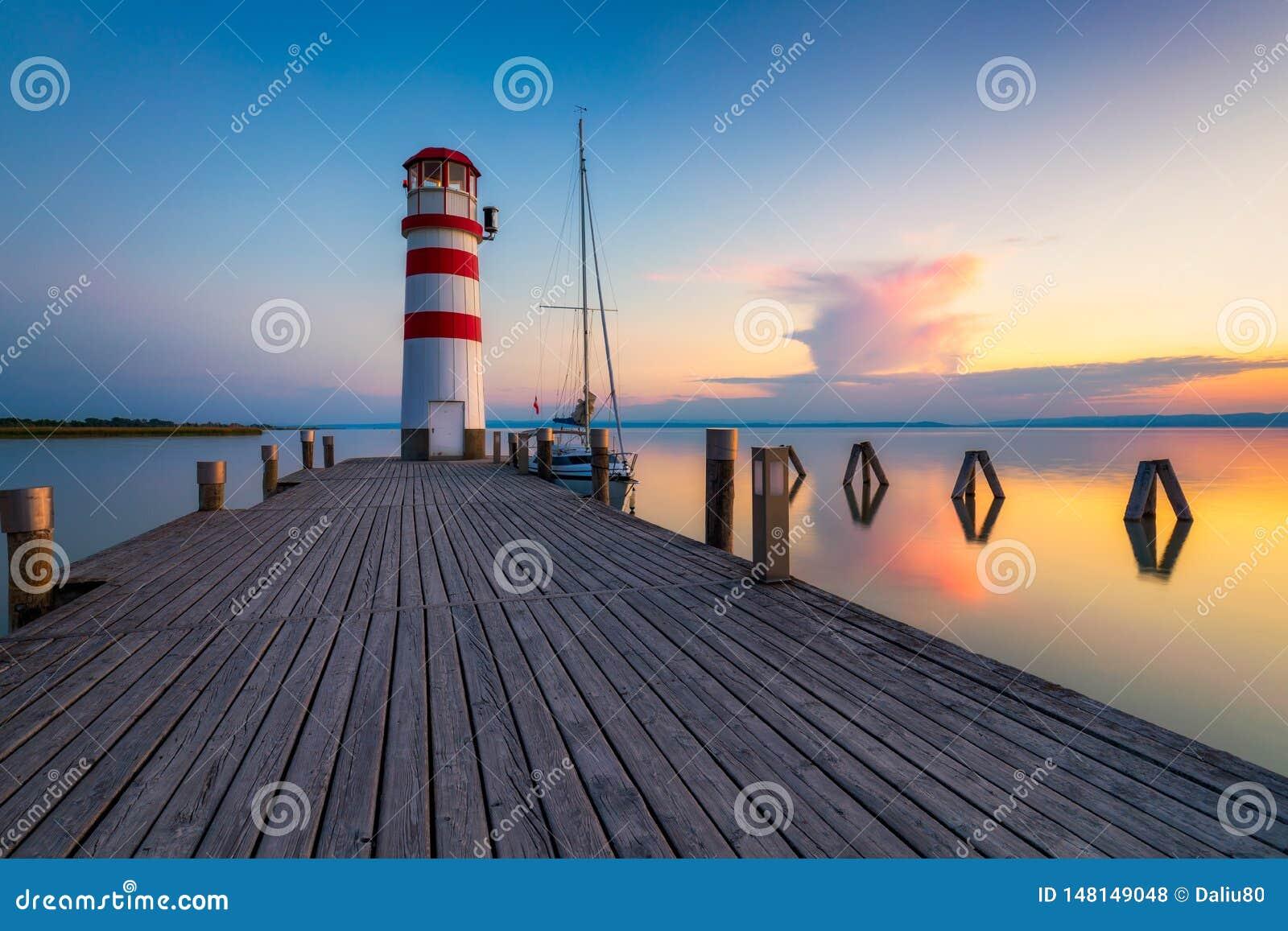 Ο φάρος στη λίμνη Neusiedl, Podersdorf AM βλέπει, Burgenland, Αυστρία Φάρος στο ηλιοβασίλεμα στην Αυστρία Ξύλινη αποβάθρα με το φ