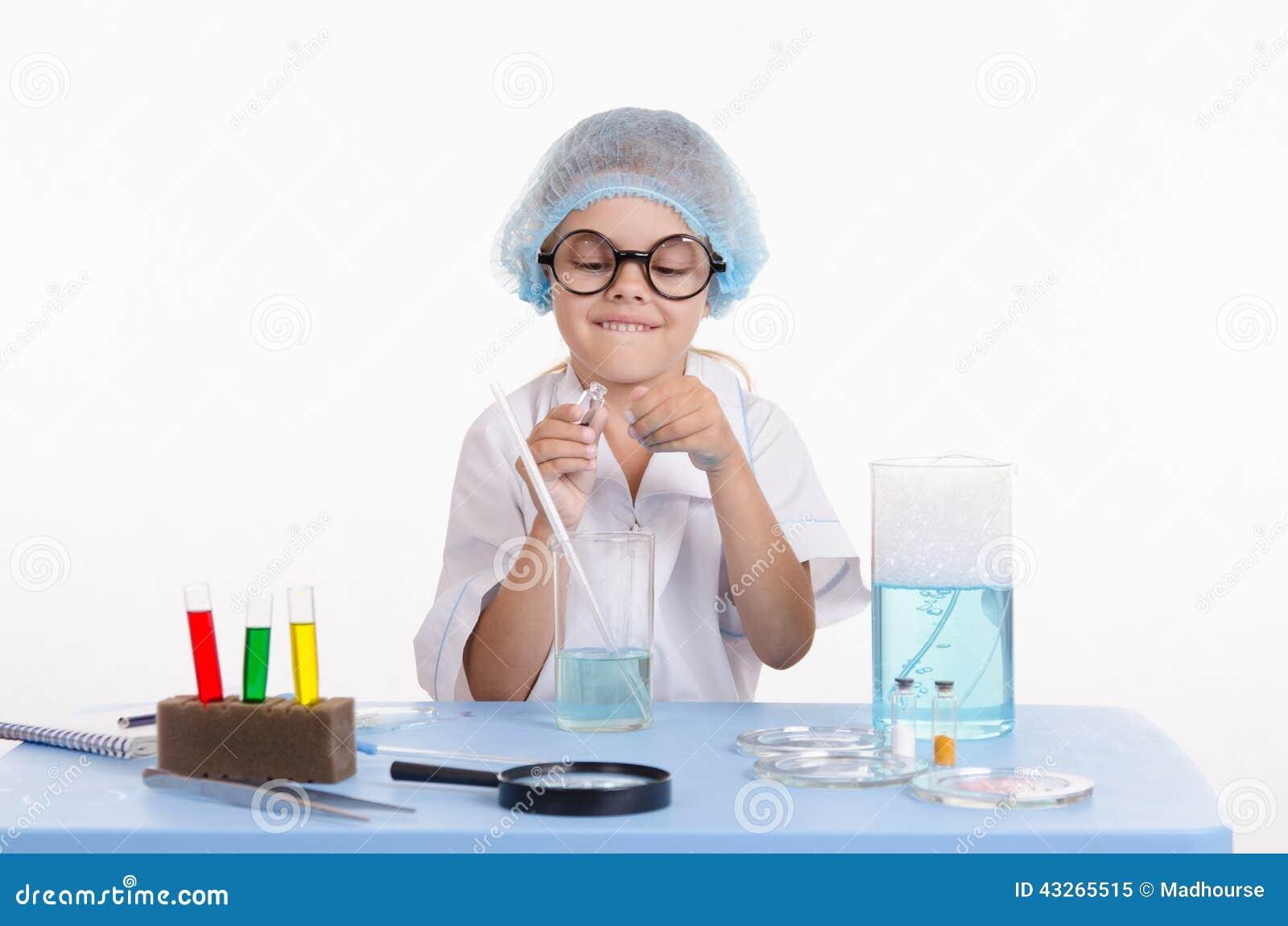 Ο φαρμακοποιός παιδιών ανοίγει τη φιάλη με το αντιδραστήριο