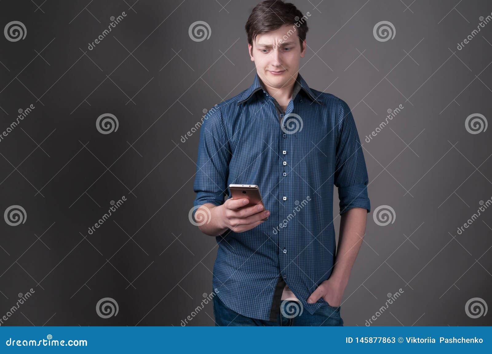 Ο φοβησμένος όμορφος νεαρός άνδρας στο μπλε πουκάμισο με παραδίδει την τσέπη εξετάζοντας το smartphone στο γκρίζο υπόβαθρο