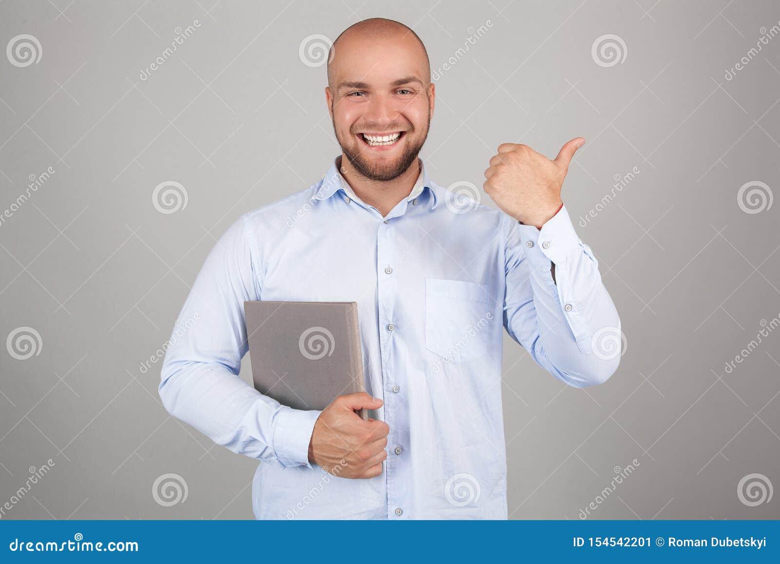Ο χαμογελώντας νέος nerdy κόκκινος γενειοφόρος μοντέρνος σπουδαστής στέκεται με τα βιβλία στο καθαρό υπόβαθρο και την περιστασιακ