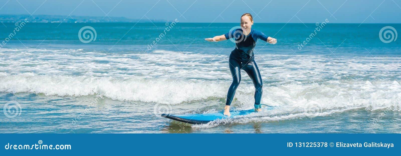 Ο χαρούμενος νέος αρχάριος γυναικών surfer με την μπλε κυματωγή έχει τη διασκέδαση στα μικρά κύματα θάλασσας Ενεργός οικογενειακό