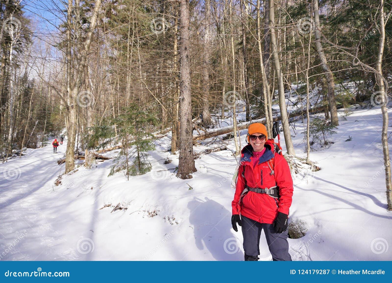 Ο χειμερινός οδοιπόρος σταματά inbitter κρύο για να γιορτάζει τη χειμερινή ηλιοφάνεια