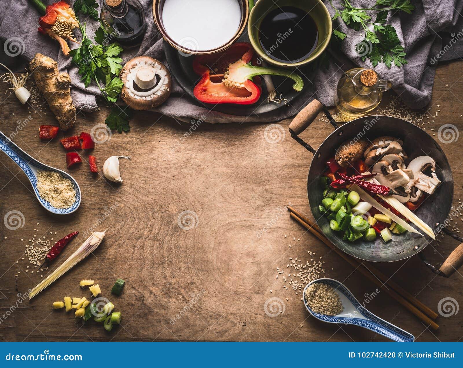 Ο χορτοφάγος ανακατώνει τη μαγειρεύοντας προετοιμασία τηγανητών στο ξύλινο υπόβαθρο με τα διάφορα λαχανικά, wok, το γάλα καρύδων,
