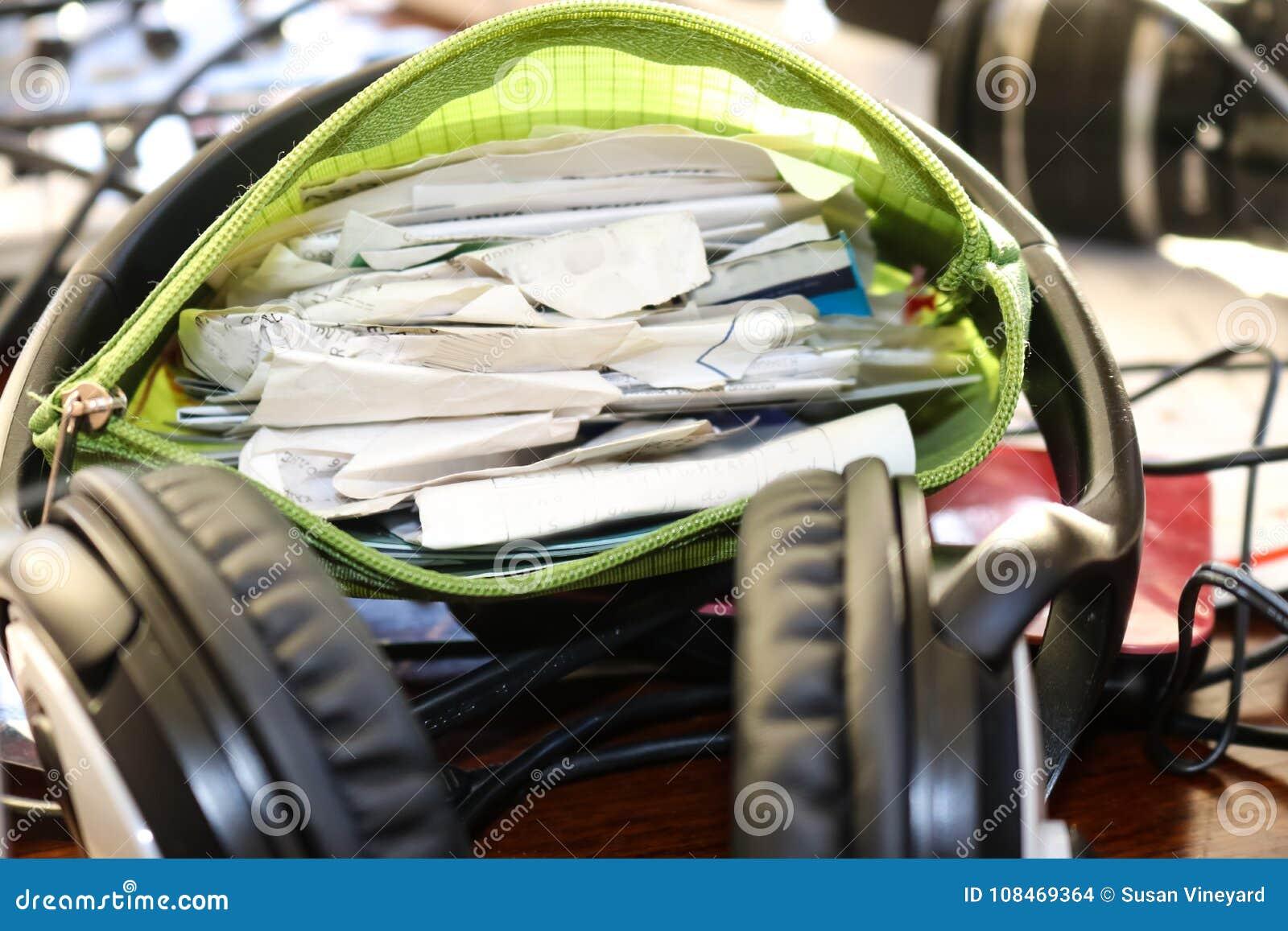 Ο χρόνος να γίνει η δαπάνη υποβάλλει έκθεση - ένα πράσινο σύνολο σακουλών zippup των παραλαβών καθμένος στον κύκλο ενός ακουστικο