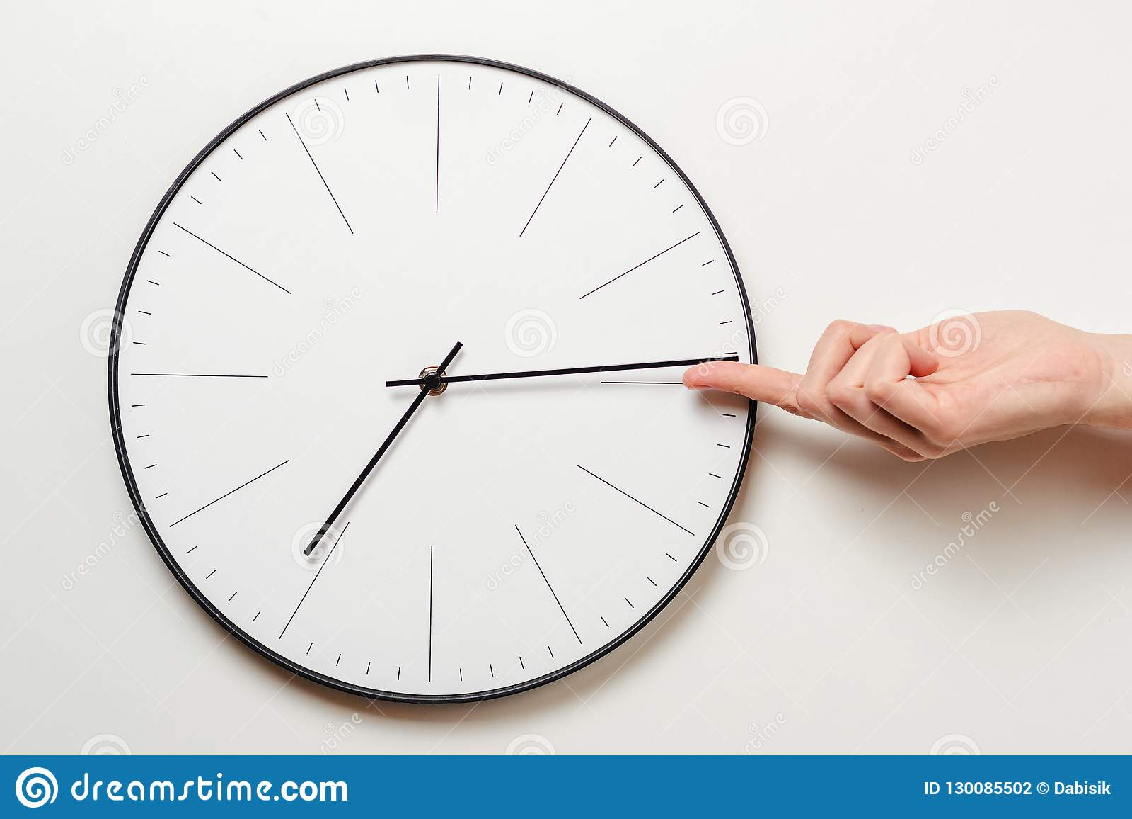 Ο χρόνος στάσεων χεριών γυναικών στο στρογγυλό ρολόι, θηλυκό δάχτυλο παίρνει το μικρό βέλος της πλάτης ρολογιών, της χρονικής δια