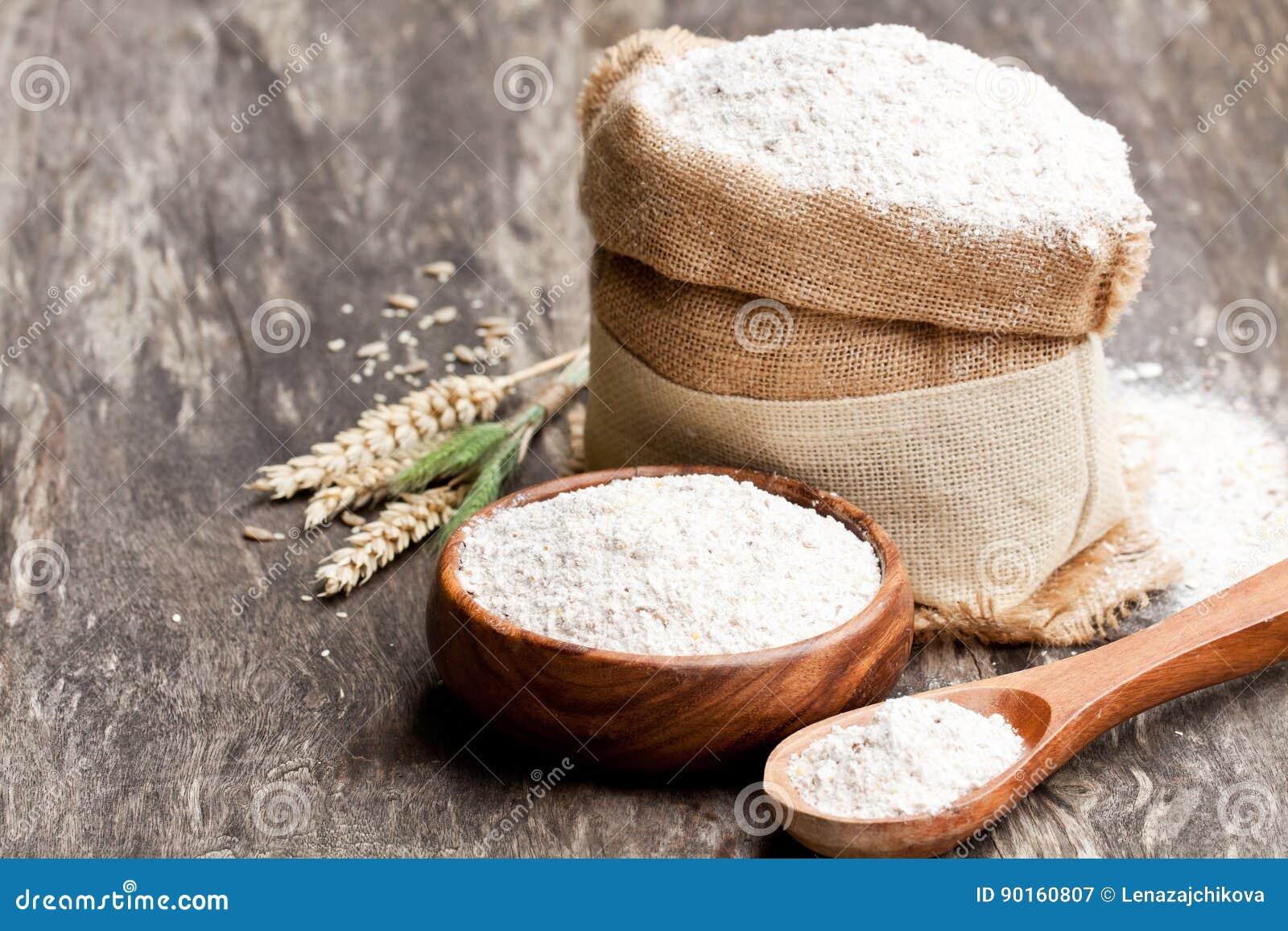 Ολόκληρο αλεύρι σιταριού στα αυτιά ξύλινων κύπελλων και sackcloth bagwith