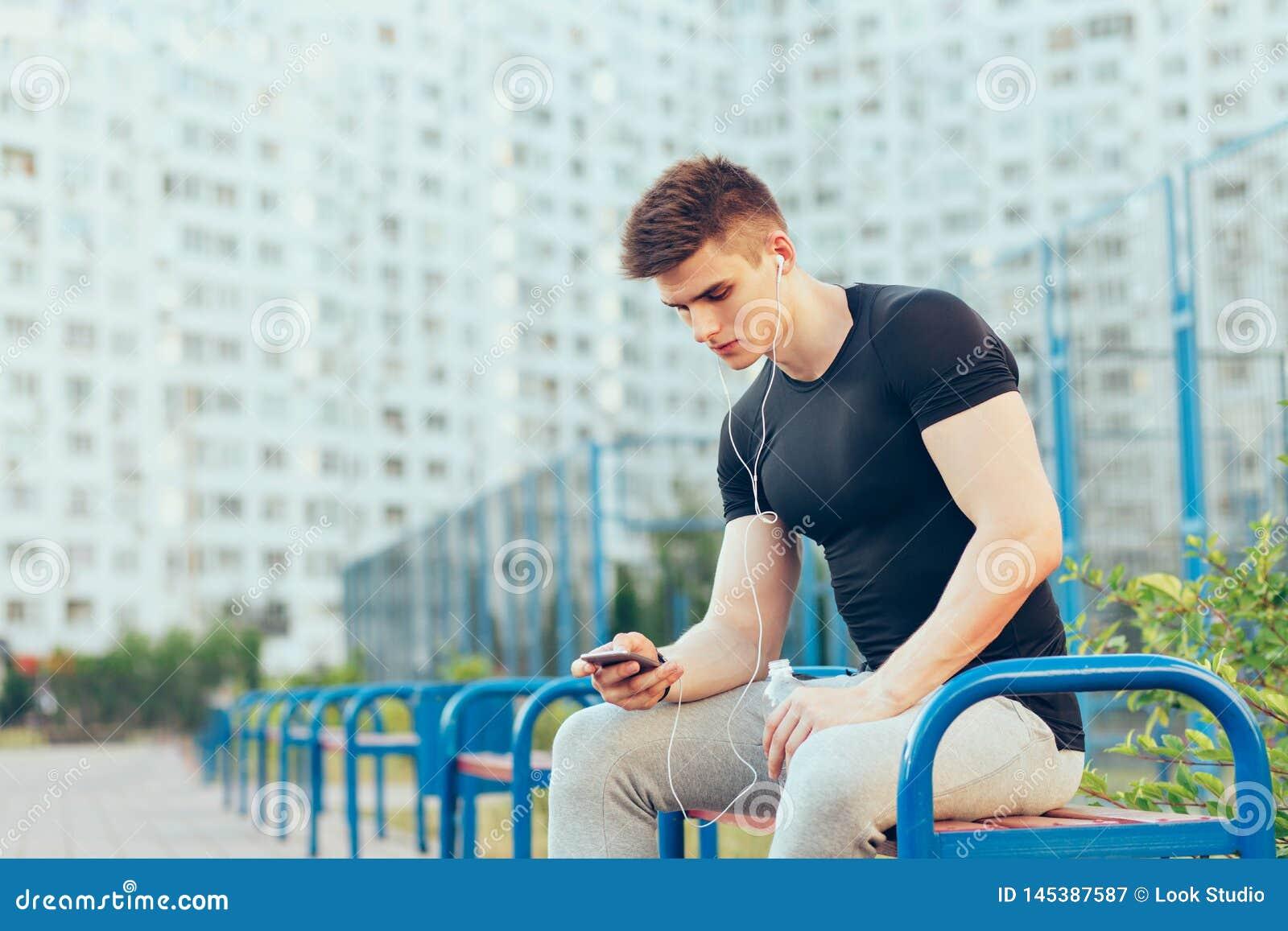 Ο όμορφος τύπος στην αθλητική μαύρη μπλούζα και τα γκρίζα αθλητικά εσώρουχα κάθεται στον πάγκο στο υπόβαθρο πόλεων και σταδίων Εί