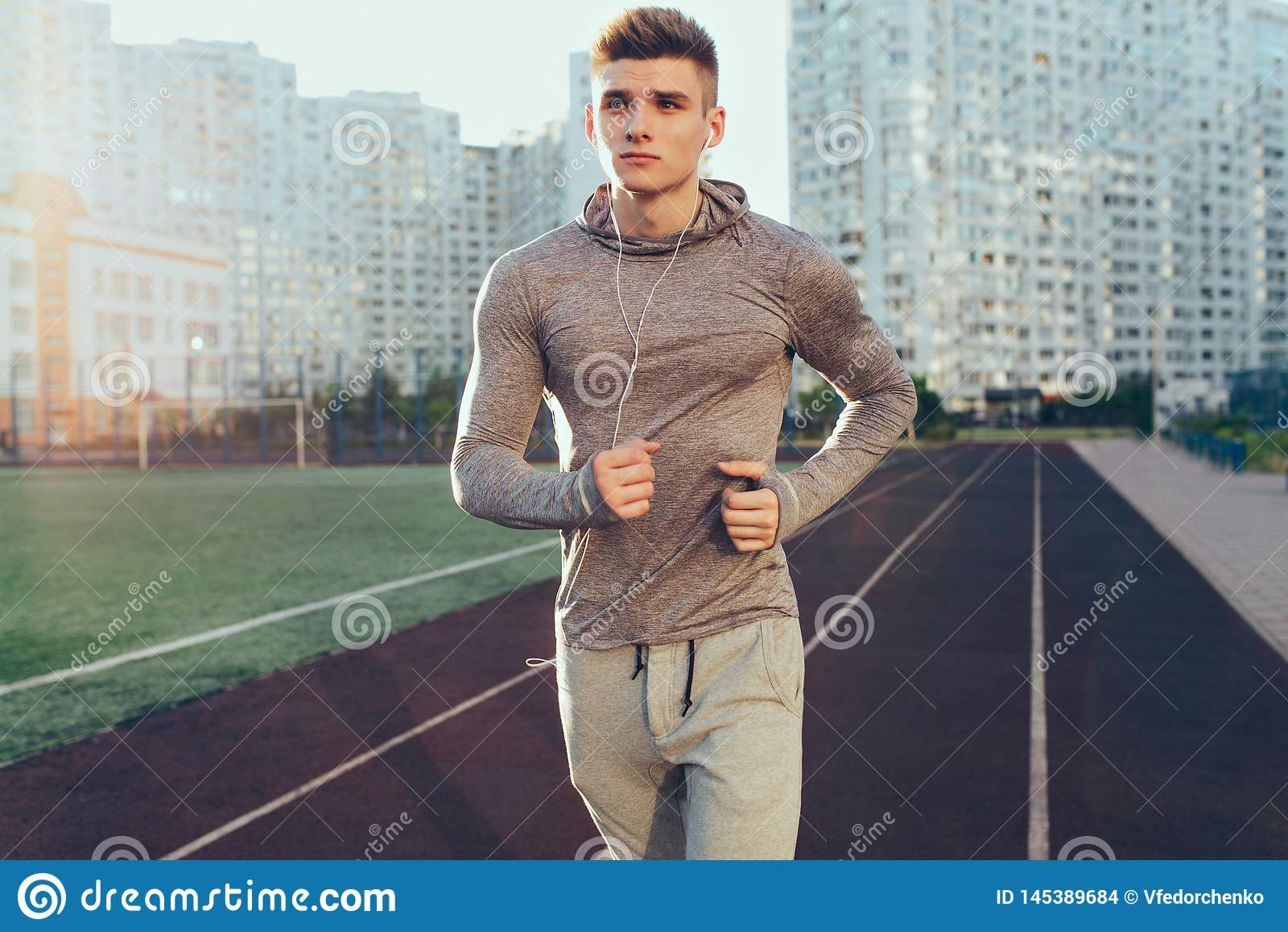 Ο όμορφος τύπος στο γκρίζο αθλητικό κοστούμι τρέχει στο workout το πρωί στο στάδιο Ακούει τη μουσική κατευθείαν
