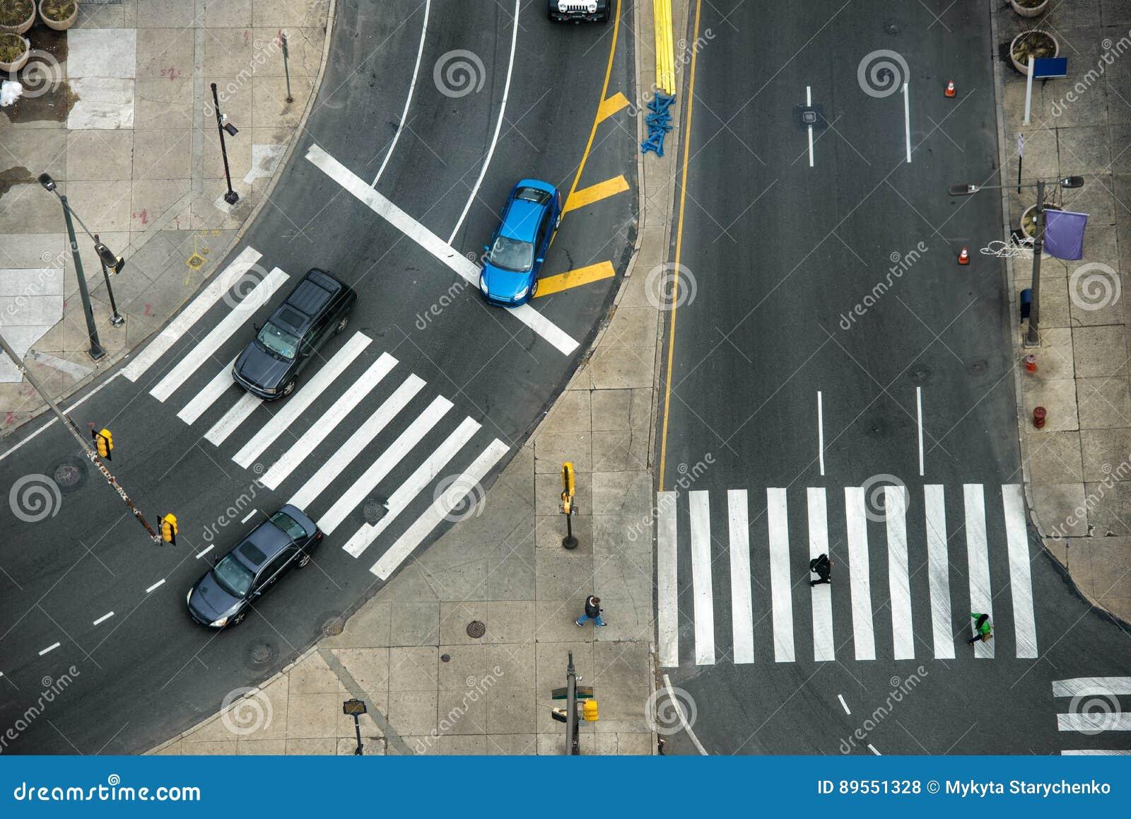 Οδός πόλεων με τις διαβάσεις πεζών στο δρόμο ασφάλτου και την κυκλοφορία αυτοκινήτων