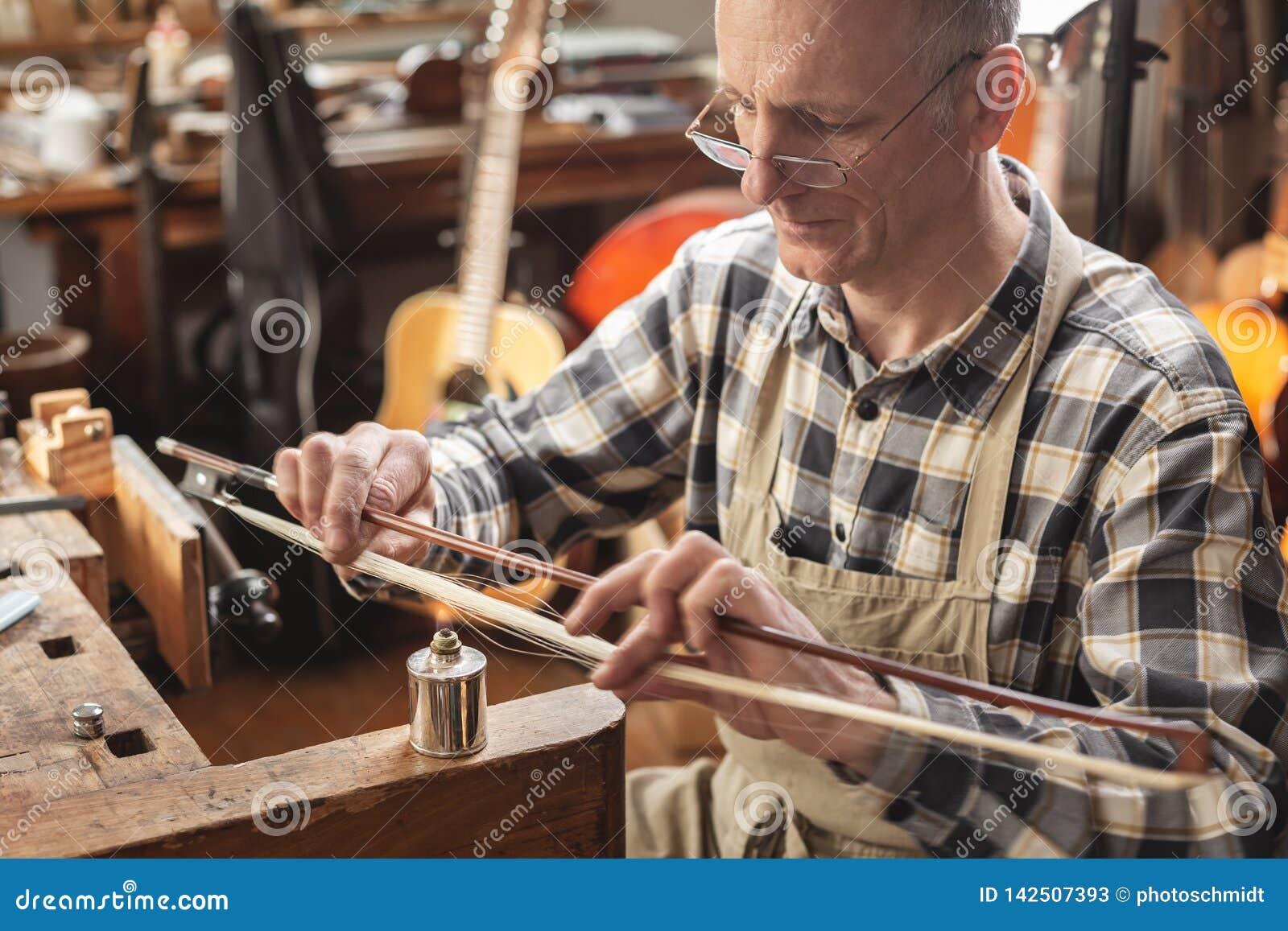 Ο ώριμος κατασκευαστής οργάνων μέσα σε ένα αγροτικό εργαστήριο θερμαίνει skillfully την τρίχα ενός τόξου βιολιών για να ρυθμίσει