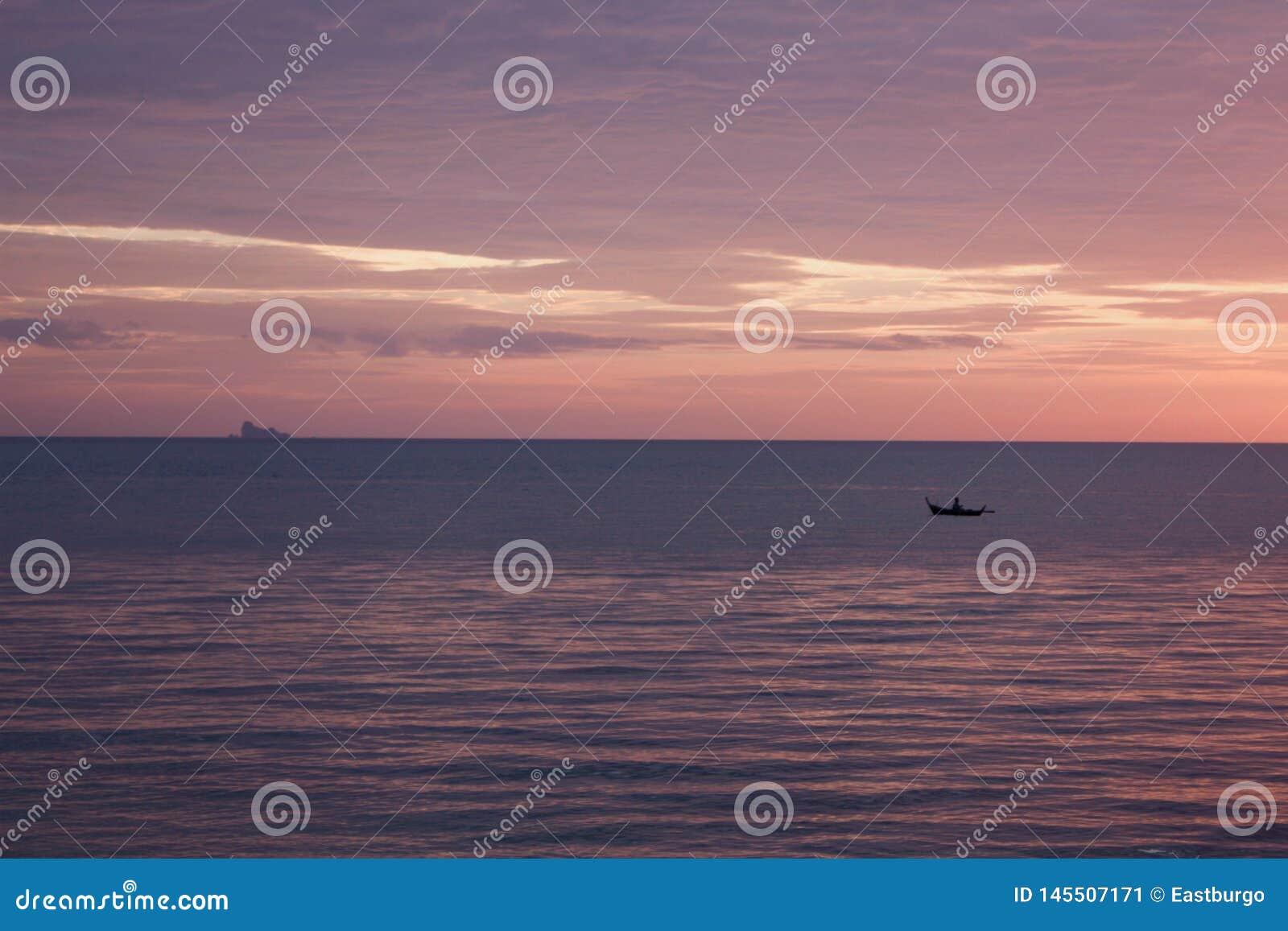 Ο Islander κωπηλατεί ένα σκαμμένο έξω κανό στο ηλιοβασίλεμα