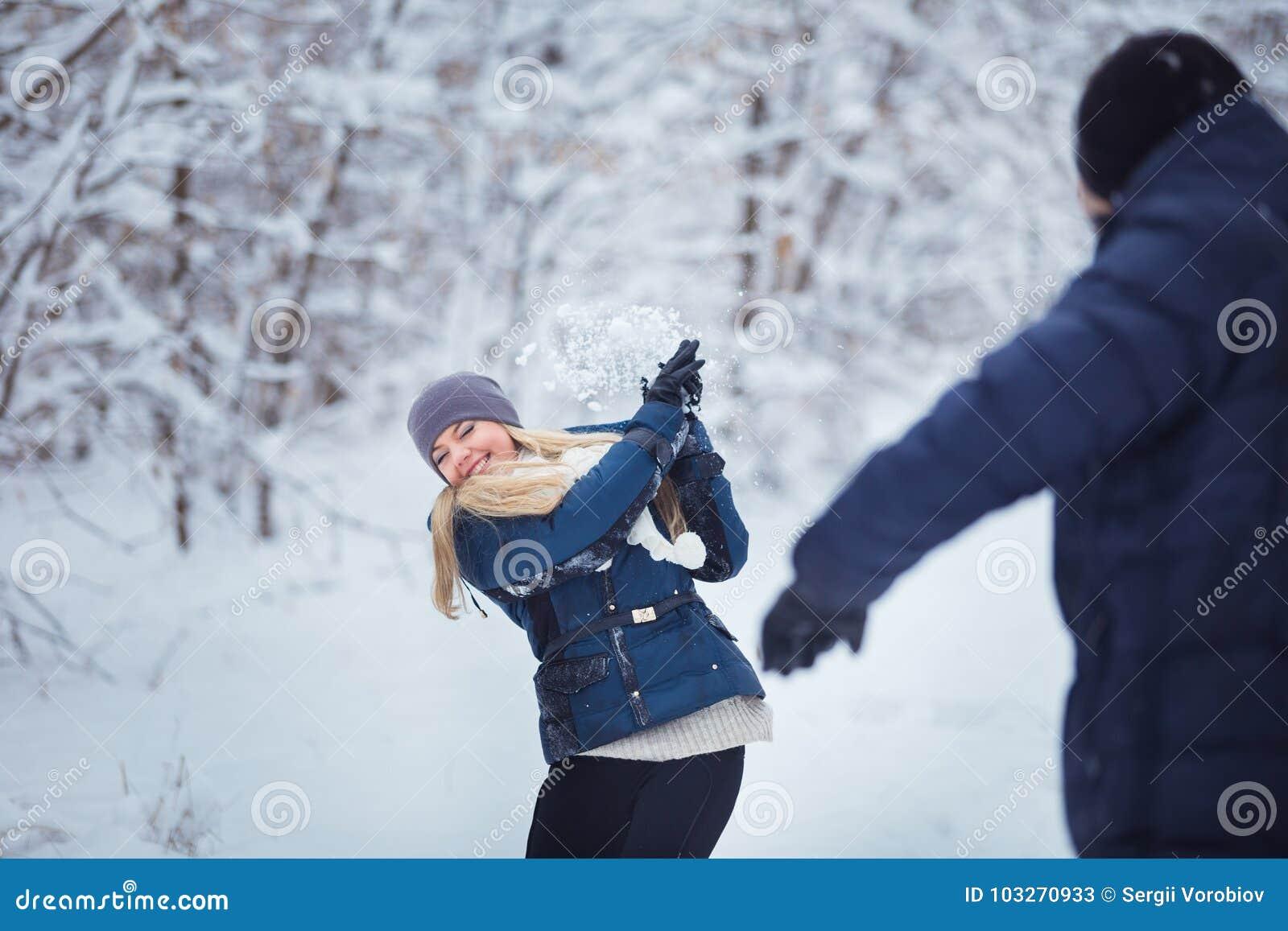 Πάλη χιονιών Χειμερινό ζεύγος που έχει το παιχνίδι διασκέδασης στο χιόνι υπαίθρια