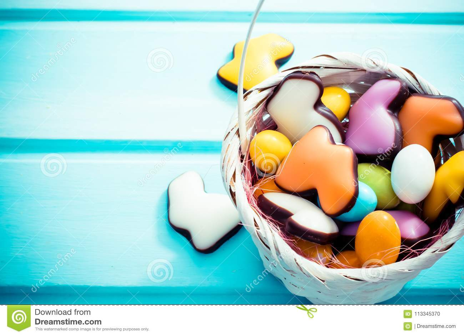 Πάσχα ευτυχές Άσπρο σύνολο καλαθιών αχύρου των αυγών και των κουνελιών γλυκών colorfull στο ανοικτό μπλε υπόβαθρο Copyspace