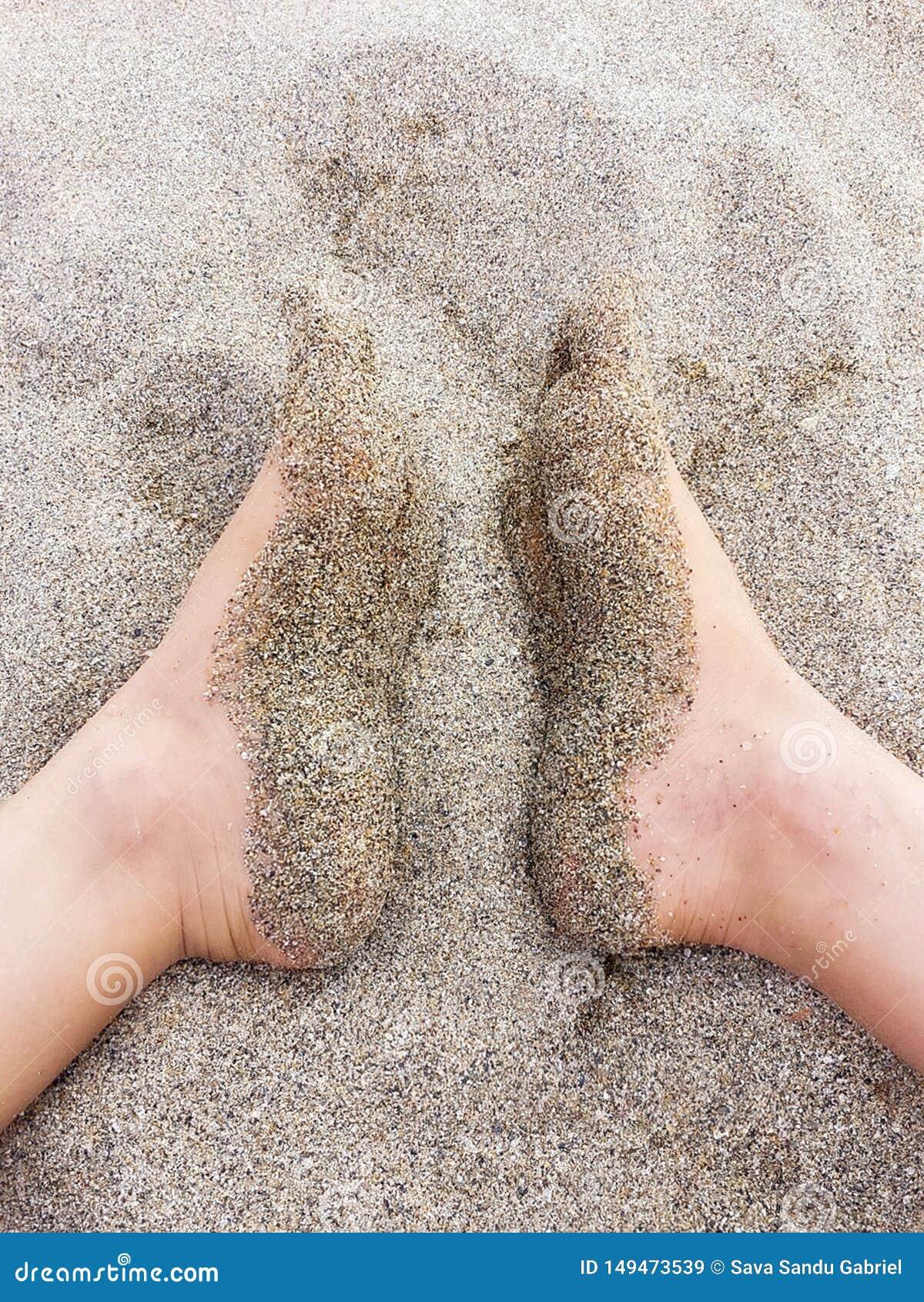 Πέλματα των ποδιών που καλύπτονται με την ξηρά άμμο
